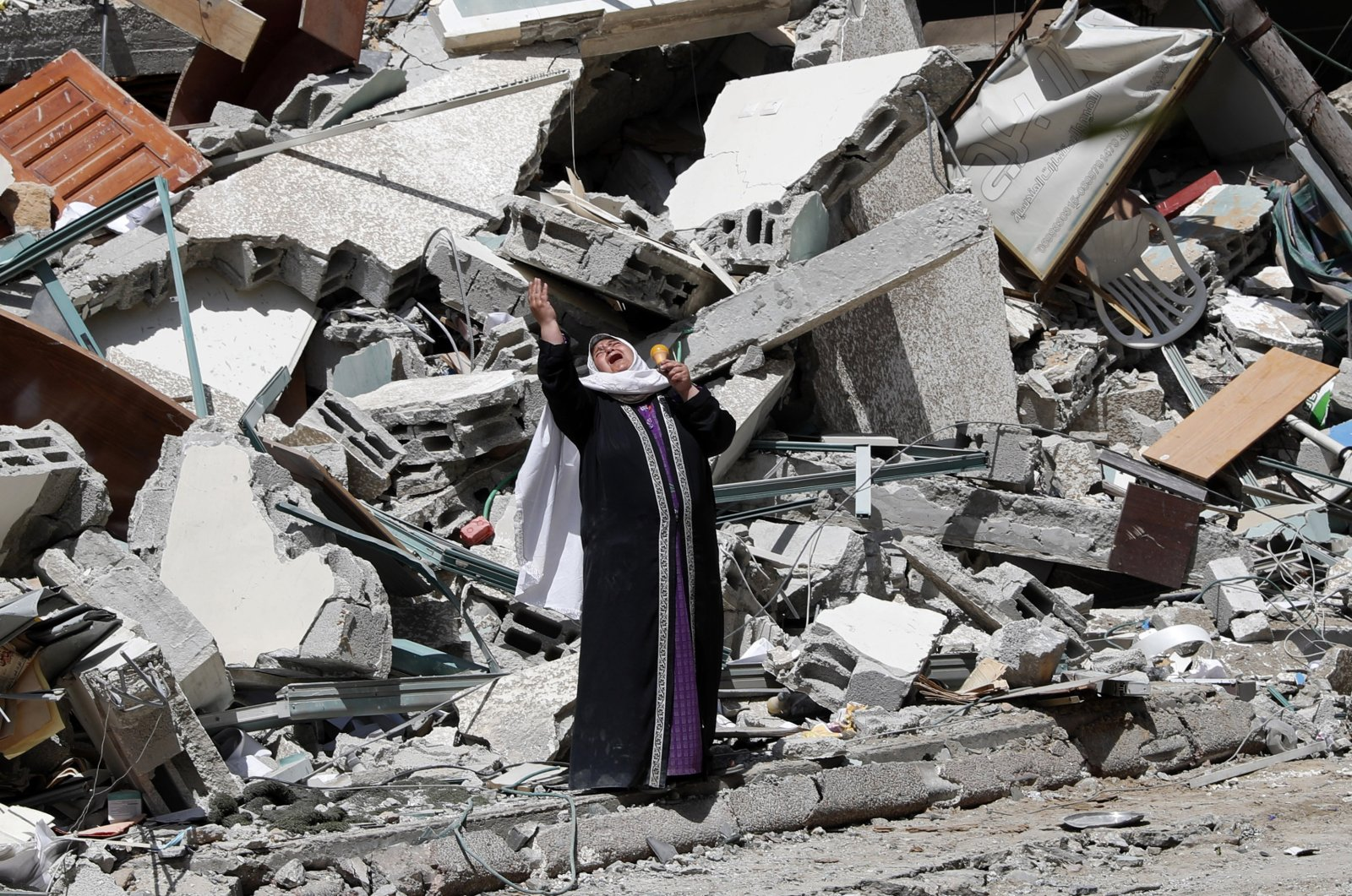A woman reacts while standing near the rubble of a building that was destroyed by an Israeli airstrike in the Gaza Strip, Palestine, May 16, 2021. (AP Photo)