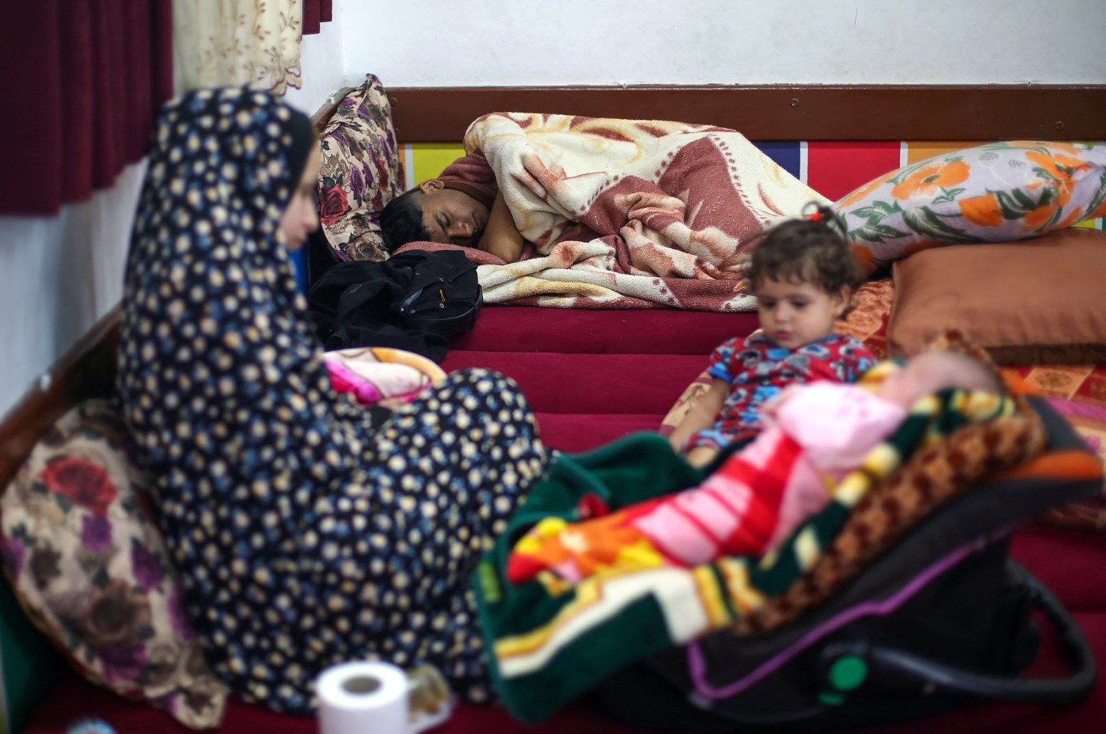 A Palestinian man, who fled his home due to Israeli air and artillery strikes, sleeps in a United Nations-run school where he takes refuge with his family, in Gaza City, May 15, 2021. (Reuters Photo)