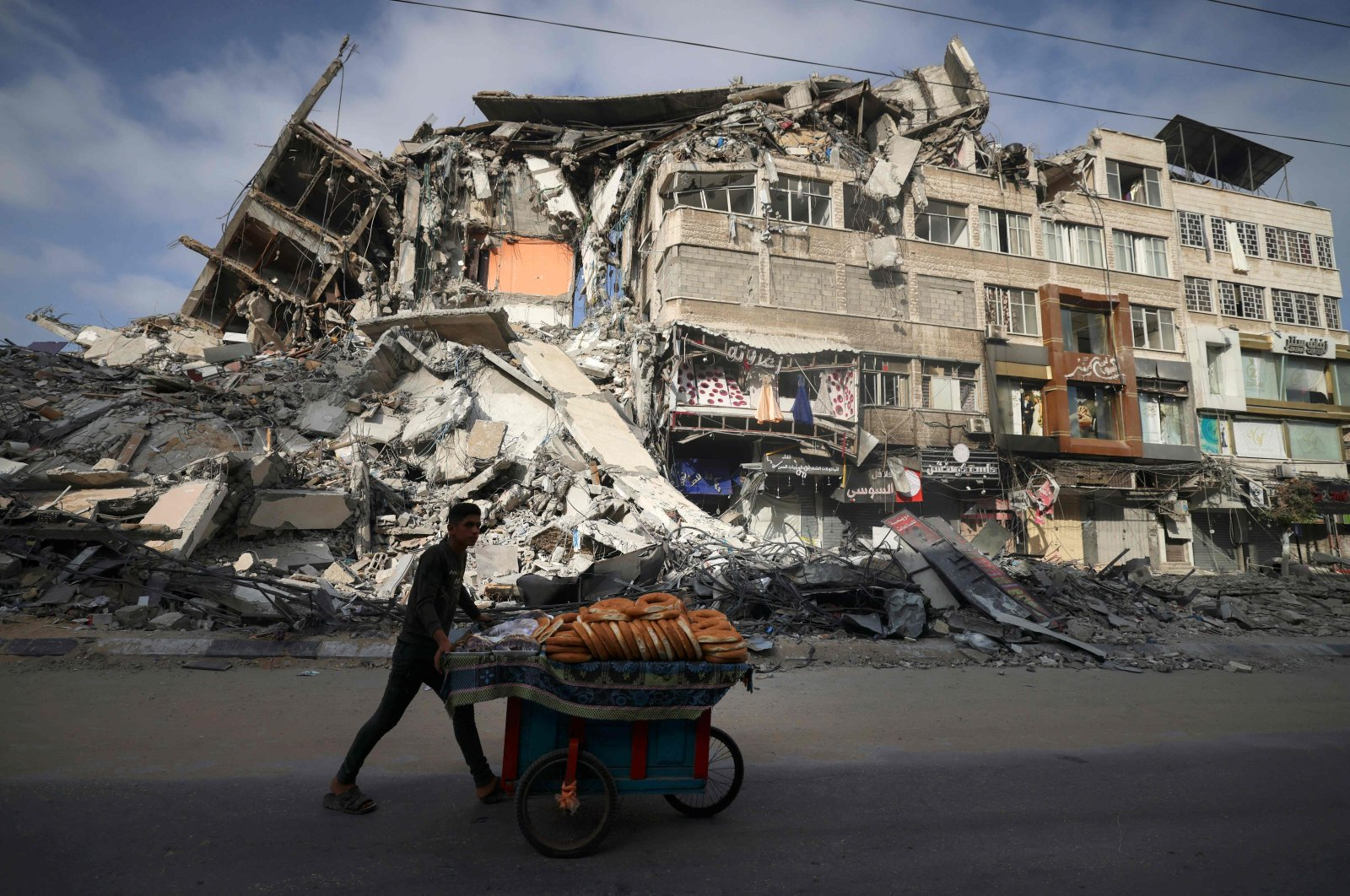 A Palestinian man walks past a building destroyed by an Israeli airstrike in Gaza Strip, Palestine, May 20, 2021. (AFP Photo)
