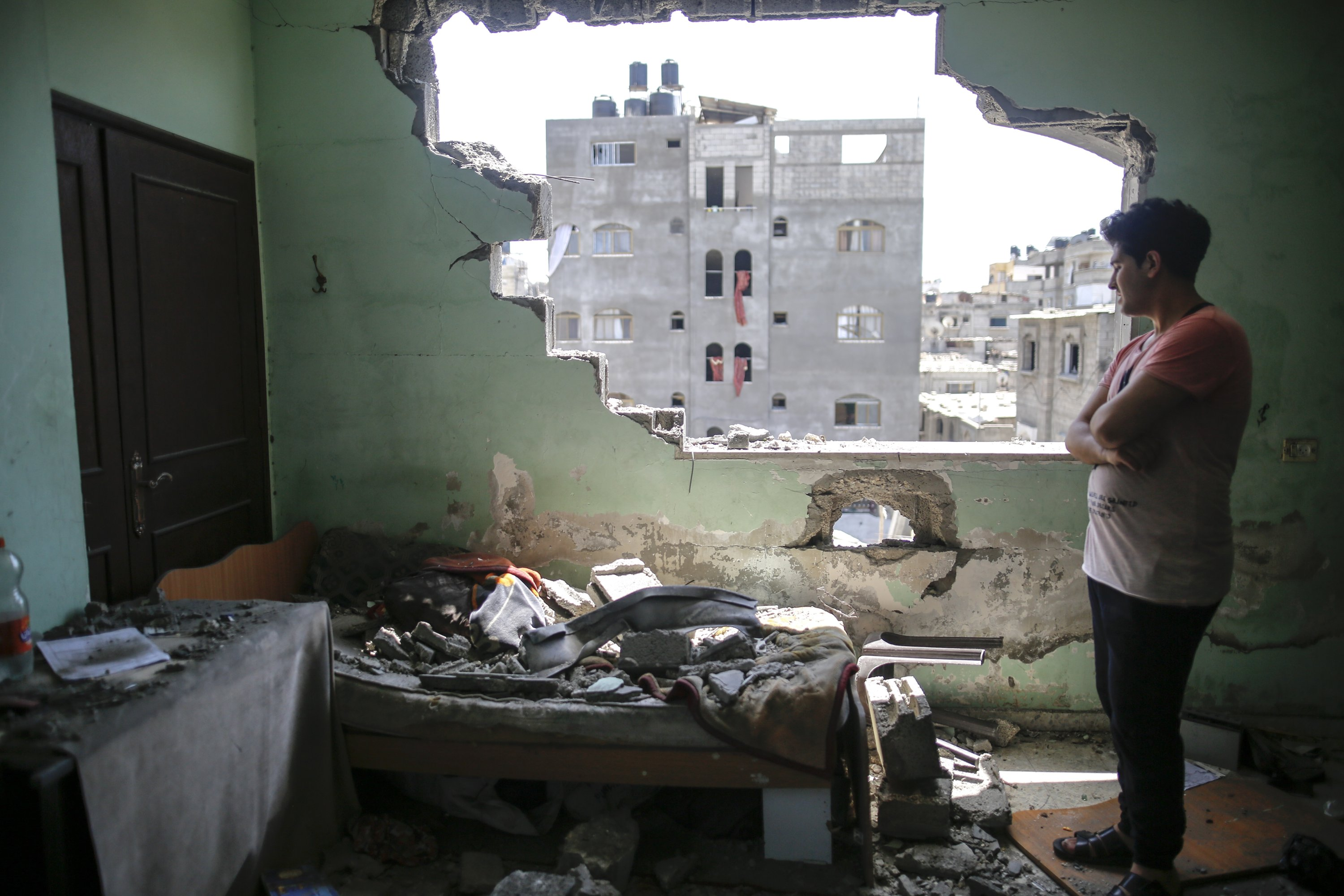 A Palestinian man inspects the damage in his room after Israeli airstrikes on his neighborhood in Gaza Strip, Palestine, May 20, 2021. (Photo by Getty Images)