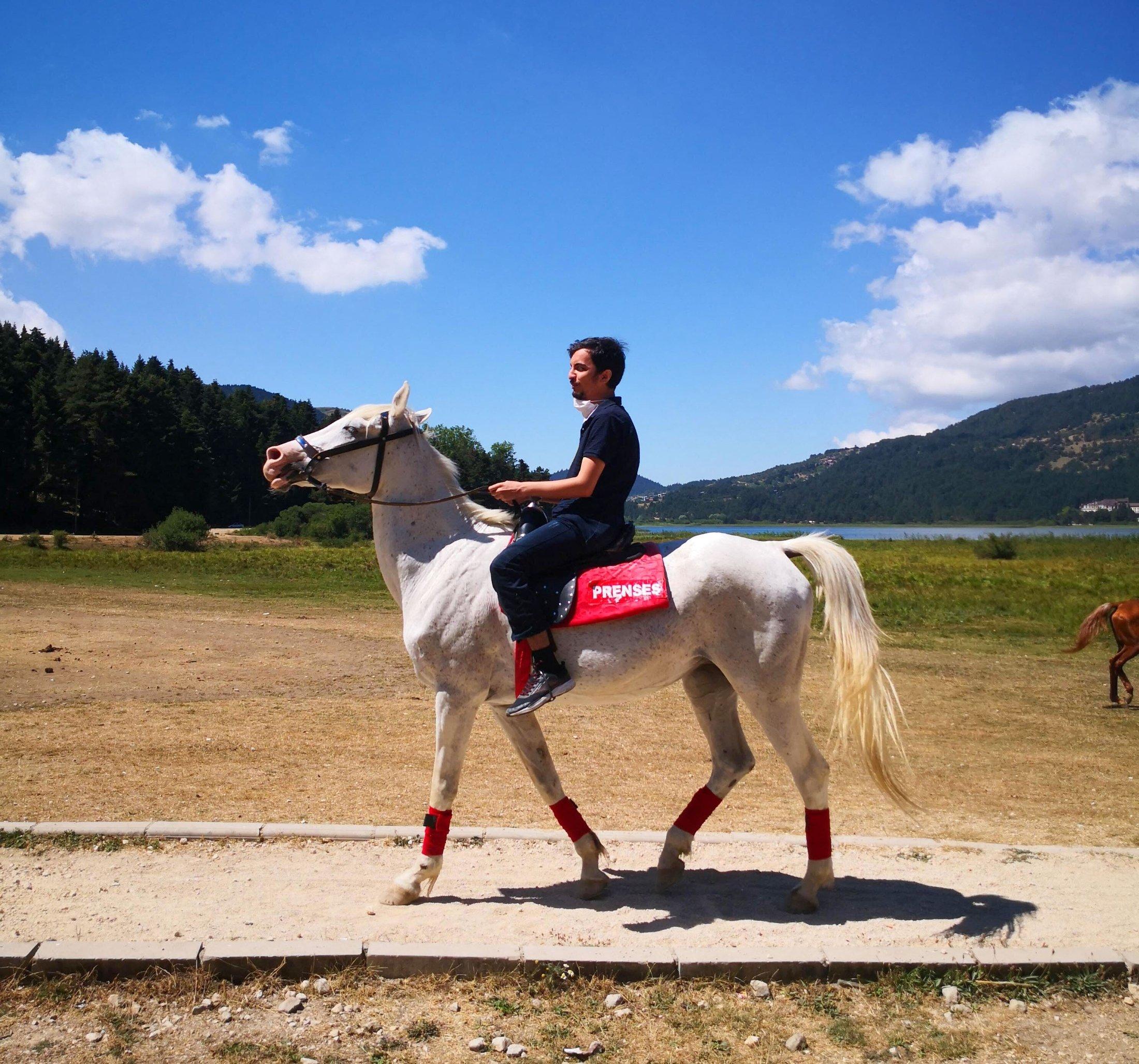 "A young man rides atop a white horse named ""Princess"" around Lake Abant, Bolu, Turkey, Aug. 16, 2020. (Photo by Ahmet Koçak)"