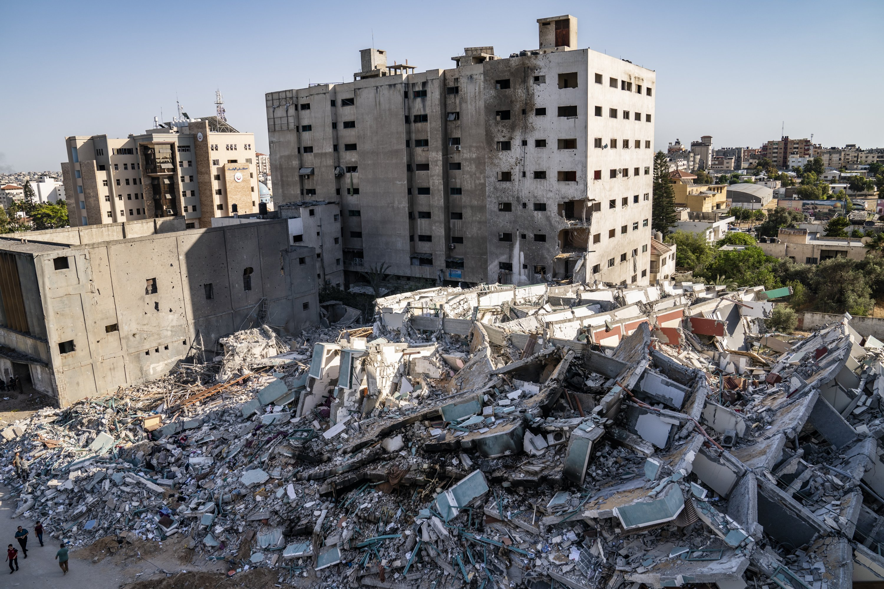 People walk past the rubble of the al-Jalaa building, which housed the Associated Press bureau in Gaza City for 15 years, that was destroyed in a previous airstrike following a cease-fire reached after an 11-day war between Gaza's Hamas rulers and Israel, in Gaza City, Palestine, May 21, 2021. (AP Photo)