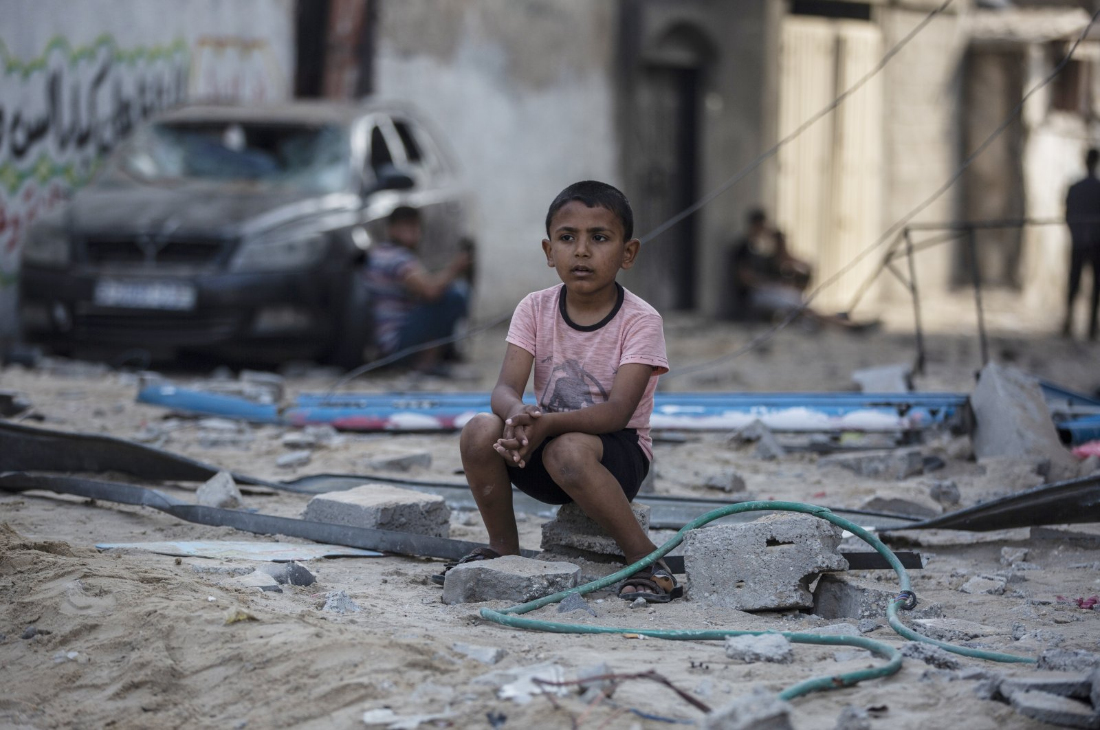 A Palestinian boy sits looking at others inspecting the damage of their shops following Israeli airstrikes on Jabaliya refugee camp, northern Gaza Strip, May 20, 2021. (AP Photo)