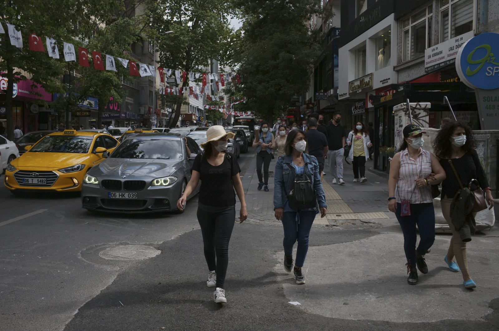 People wearing masks to help protect against the spread of the coronavirus, walk in busy traffic, two days after a 17-day full lockdown ended, Ankara, Turkey, May 18, 2021. (AP Photo)