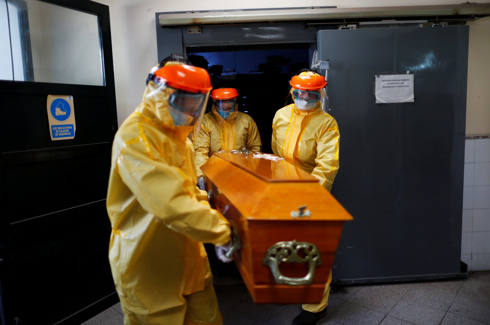 Ernesto Fabian Aguirre, a gravedigger in Memorial Cemetery, carries a coffin with his coworkers wearing protective equipment during an exercise for coronavirus disease (COVID-19) burials, after deaths surpass 70,000 amid a strong second wave of the pandemic and a slow vaccination process, in Buenos Aires, Argentina, May 17, 2021. (Reuters Photo)