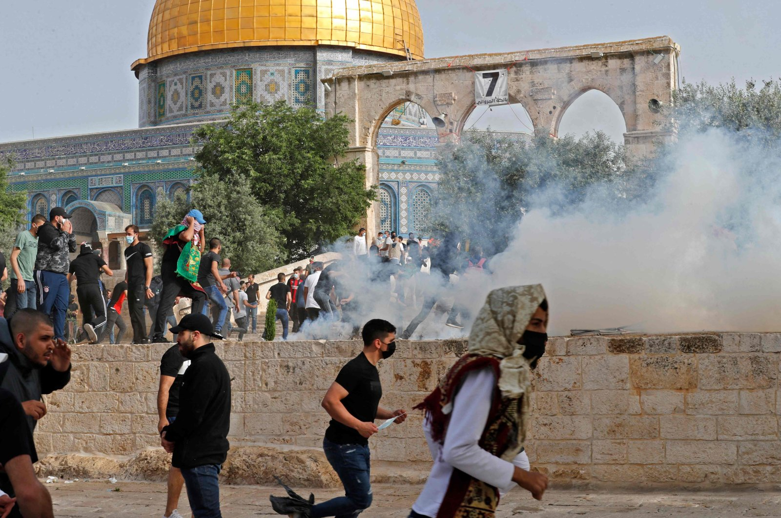 Palestinian protesters run for cover from tear gas fired by Israeli security forces amid clashes at East Jerusalem's Al-Aqsa Mosque complex, occupied Palestine, May 10, 2021. (AFP Photo)