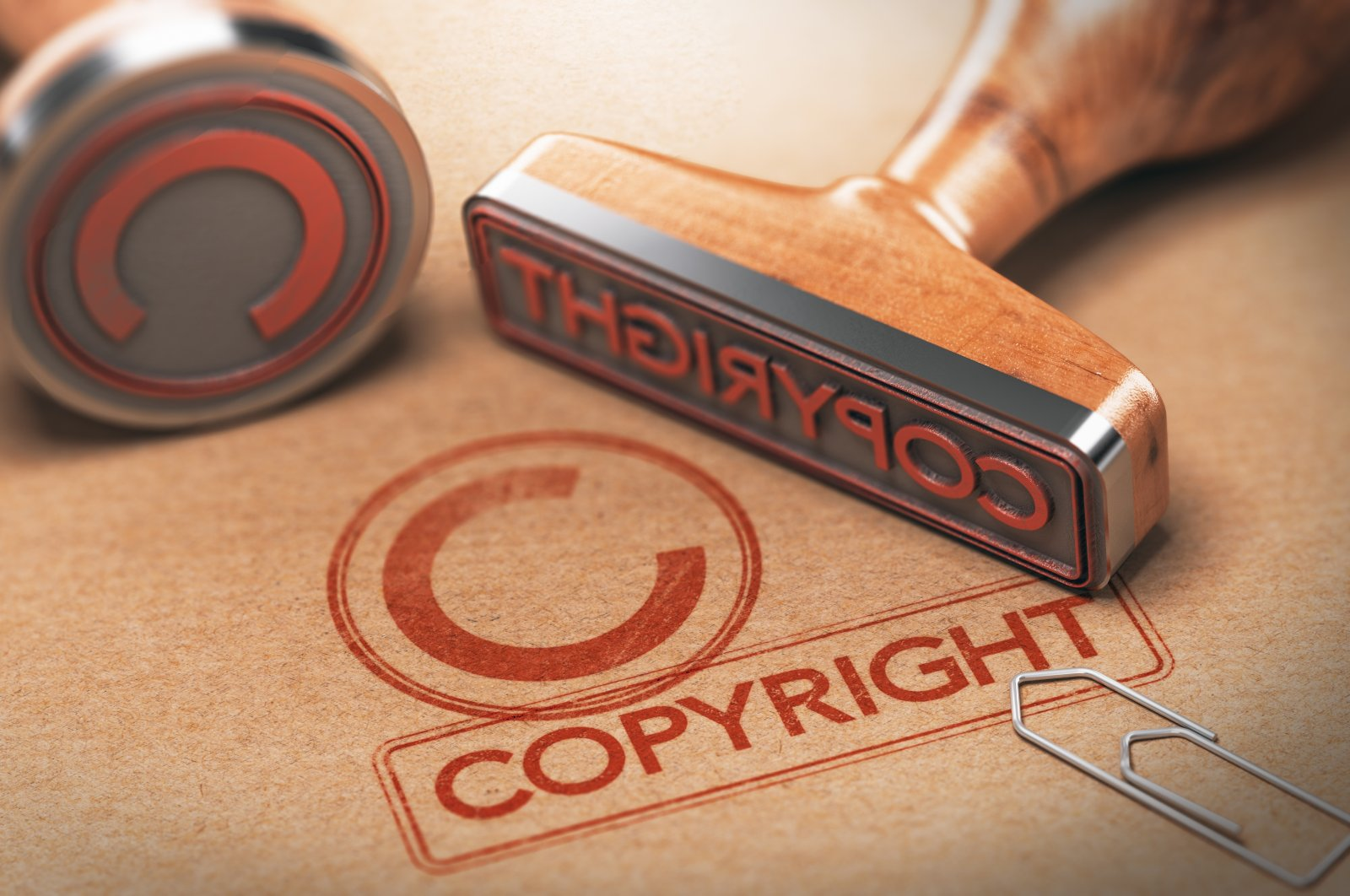 """An illustration shows the word """"copyright"""" and the term's symbol,stamped on a paper alongside their corresponding rubber stamps. (Shutterstock Photo)"""