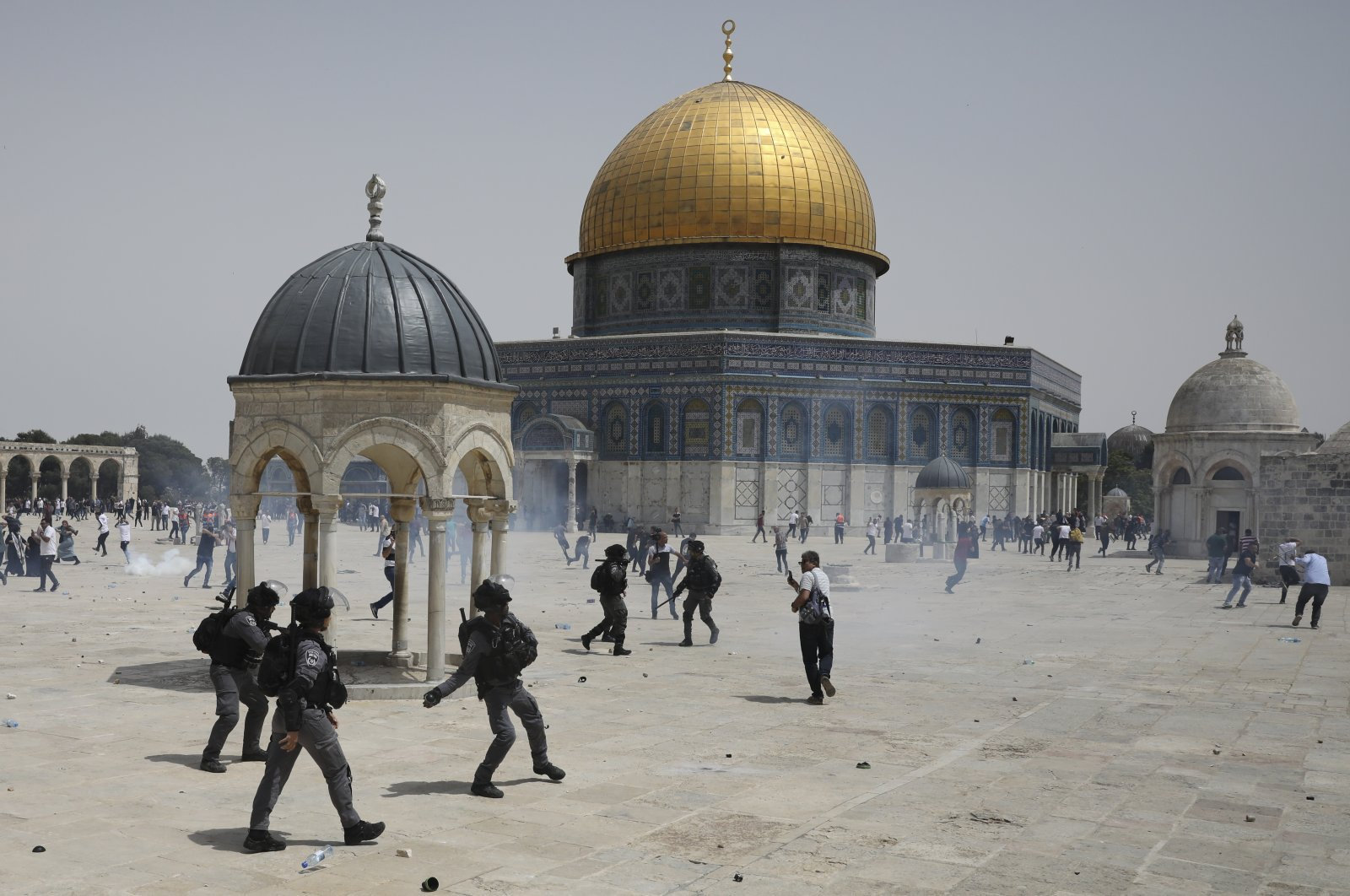 Palestinians run from sound grenades thrown by Israeli police in front of the Dome of the Rock in the al-Aqsa mosque complex in Jerusalem, Friday, May 21, 202, as a cease-fire took effect between Hamas and Israel after an 11-day war. (AP Photo)