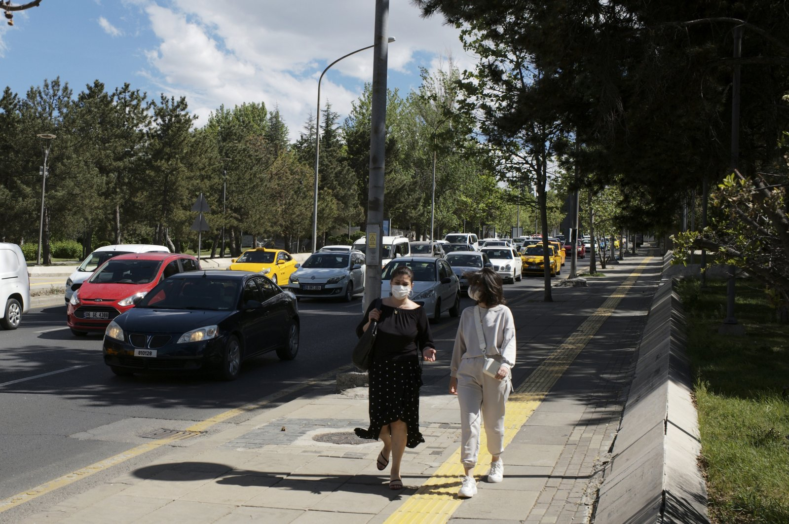 People wearing face masks to help protect against the spread of coronavirus, walk past a traffic jam hours before a weekend curfew, in Ankara, Turkey, May 21, 2021.  (AP Photo)