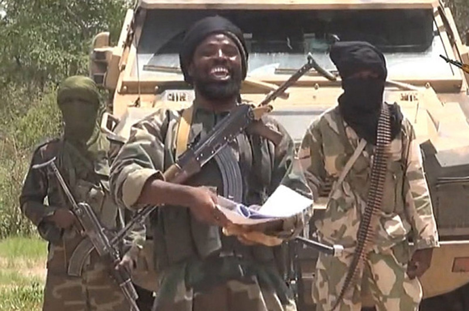 Boko Haram leader Abubakar Shekau (C) smiles in a video made and released by the terrorist group at an undisclosed location and date, in this screengrab taken on July 13, 2014. (AFP/Boko Haram/Getty Images)