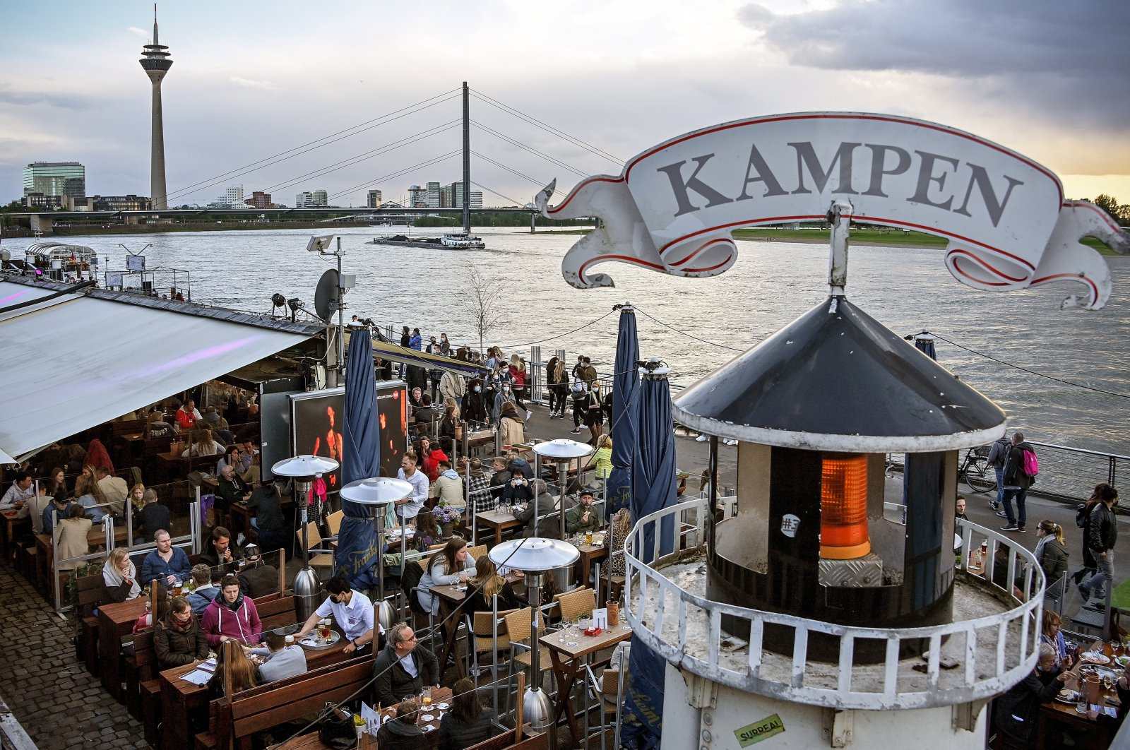 People stroll along the casemates on the banks of the Rhine in Duesseldorf, Germany, May 21, 2021. (EPA Photo)