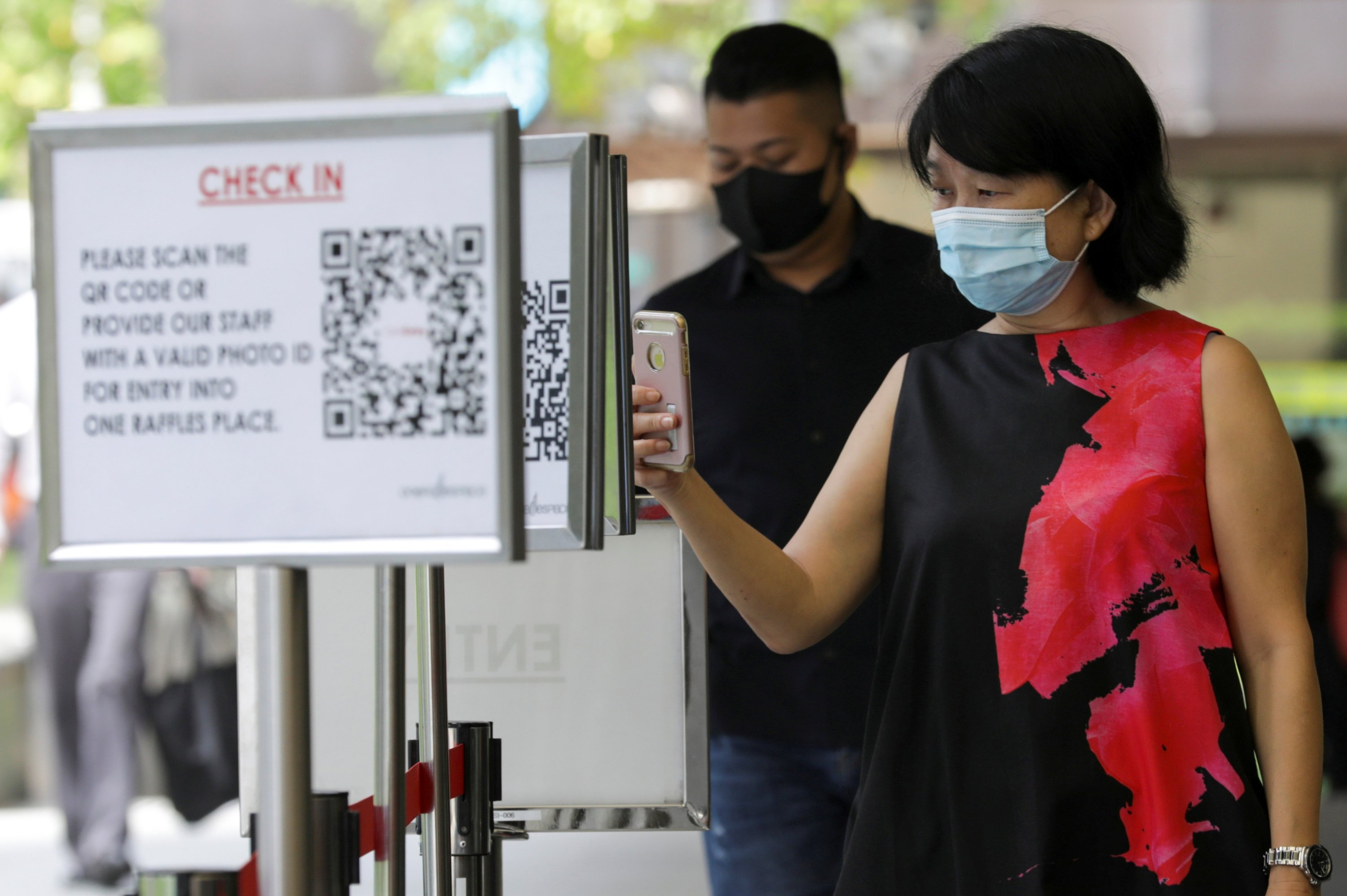 Office workers scan a Safe Entry QR code to enter a mall, amid the coronavirus disease (COVID-19) outbreak in Singapore, May 12, 2021.   (REUTERS)