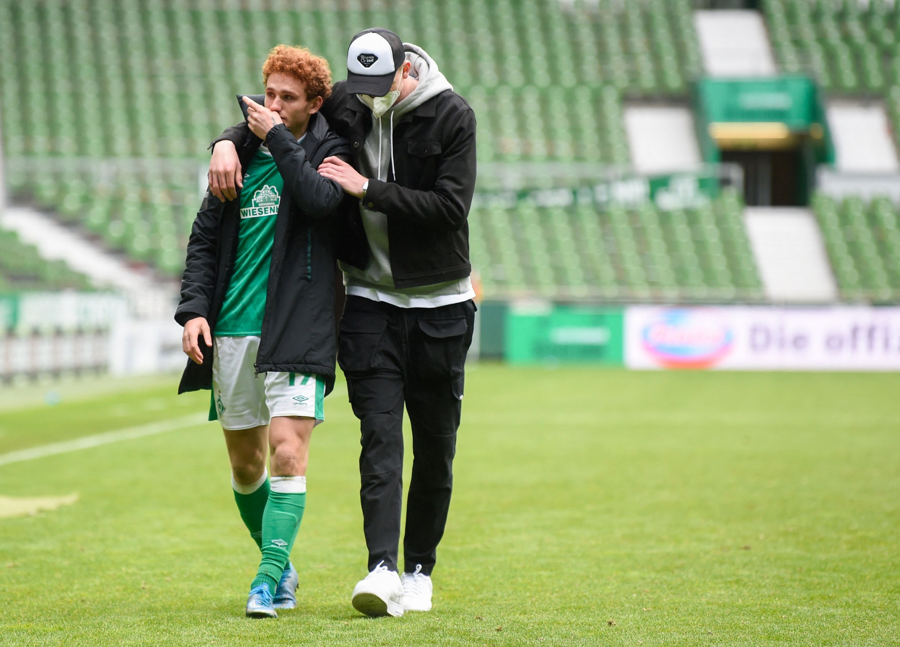 Werder Bremen's U.S. forward Joshua Sargent (L) is comforted by a team member as they leave the pitch after the German first division Bundesliga football match Borussia Monchengladbach in Bremen, Germany, May 22, 2021. (AFP Photo)
