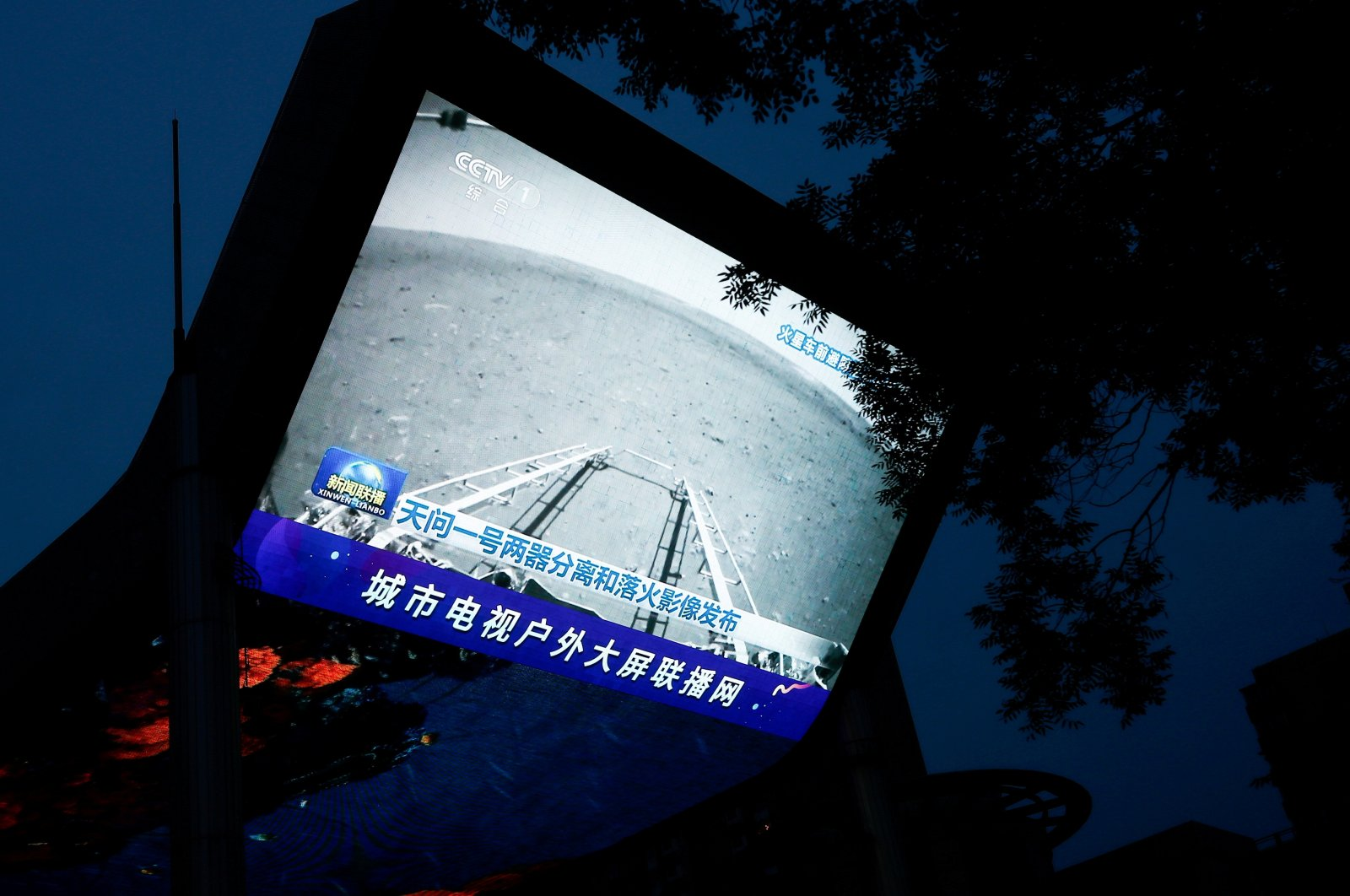 A screen broadcasts a CCTV state media news bulletin, showing an image of Mars taken by Chinese Mars rover Zhurong as part of the Tianwen-1 mission, in Beijing, China, May 19, 2021. (Reuters Photo)