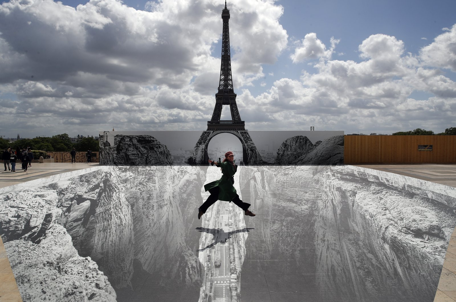 A woman jumps at Trocadero square in front of the Eiffel Tower where French artist and photographer JR set his artwork, in Paris, France, May 21, 2021. (AP Photo)