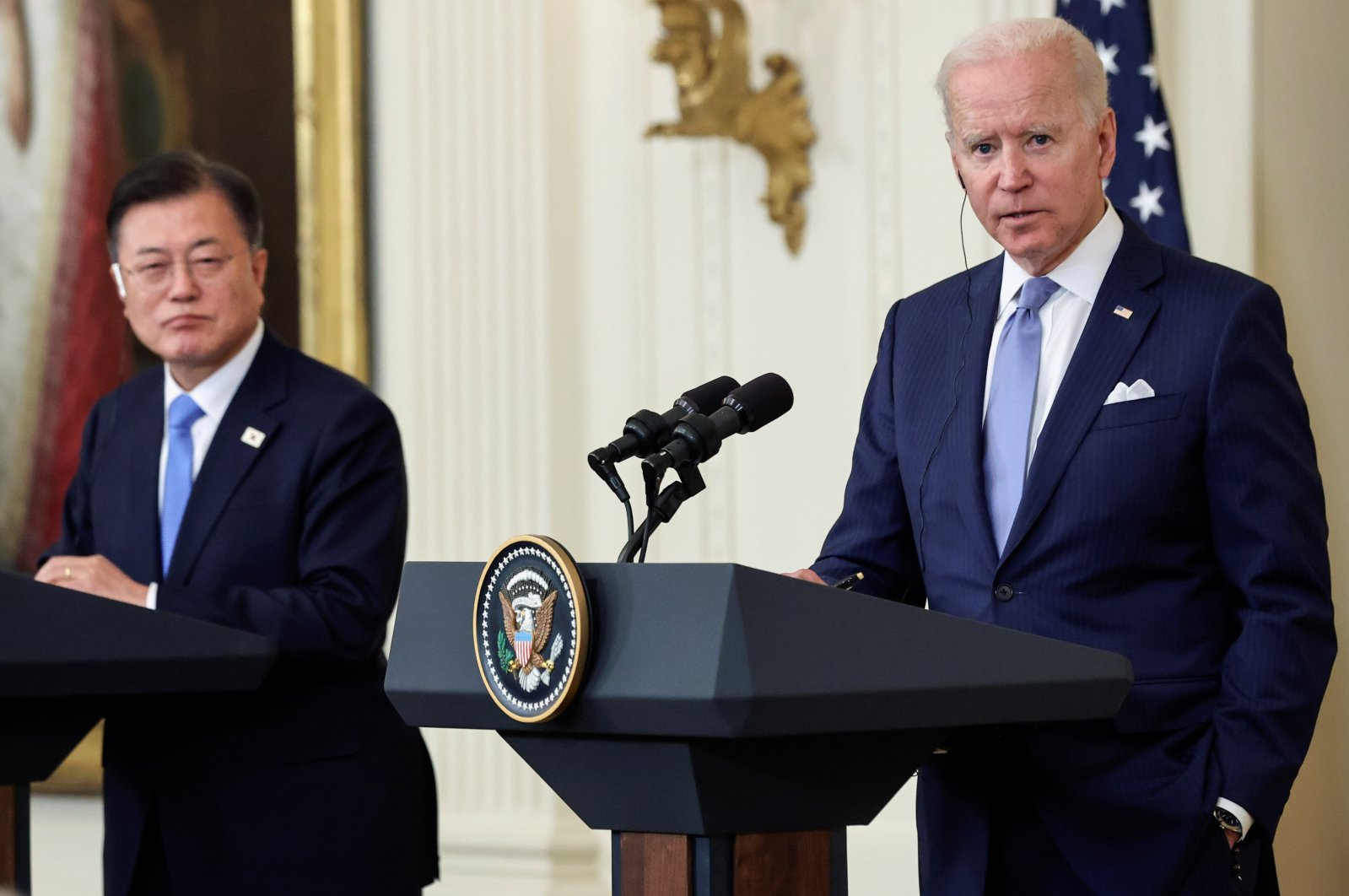 South Korean President Moon Jae-in (L) listens while U.S. President Joe Biden engages a reporter during a joint news conference after a day of meetings at the White House, in Washington, D.C., U.S., May 21, 2021. (REUTERS)
