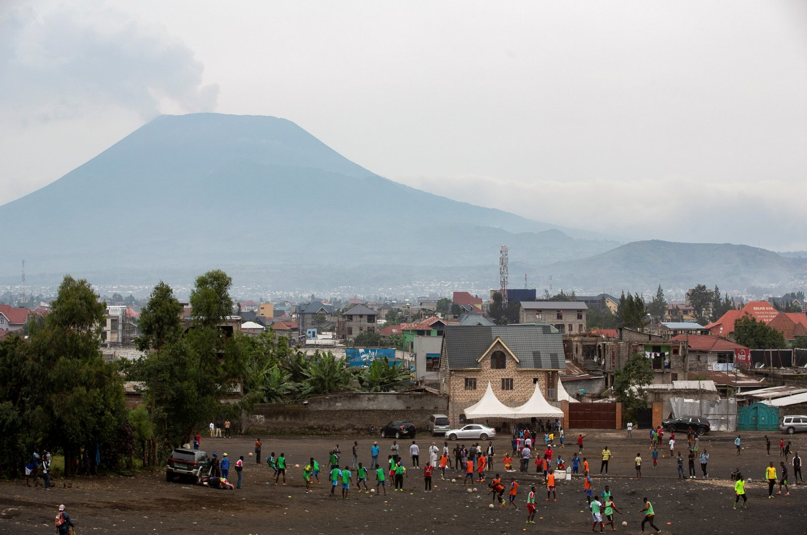 Congolese men play football with Mount Nyiragongo puffing away in the background, in Goma, eastern Democratic Republic of Congo, Feb. 18, 2021. (Reuters Photo)