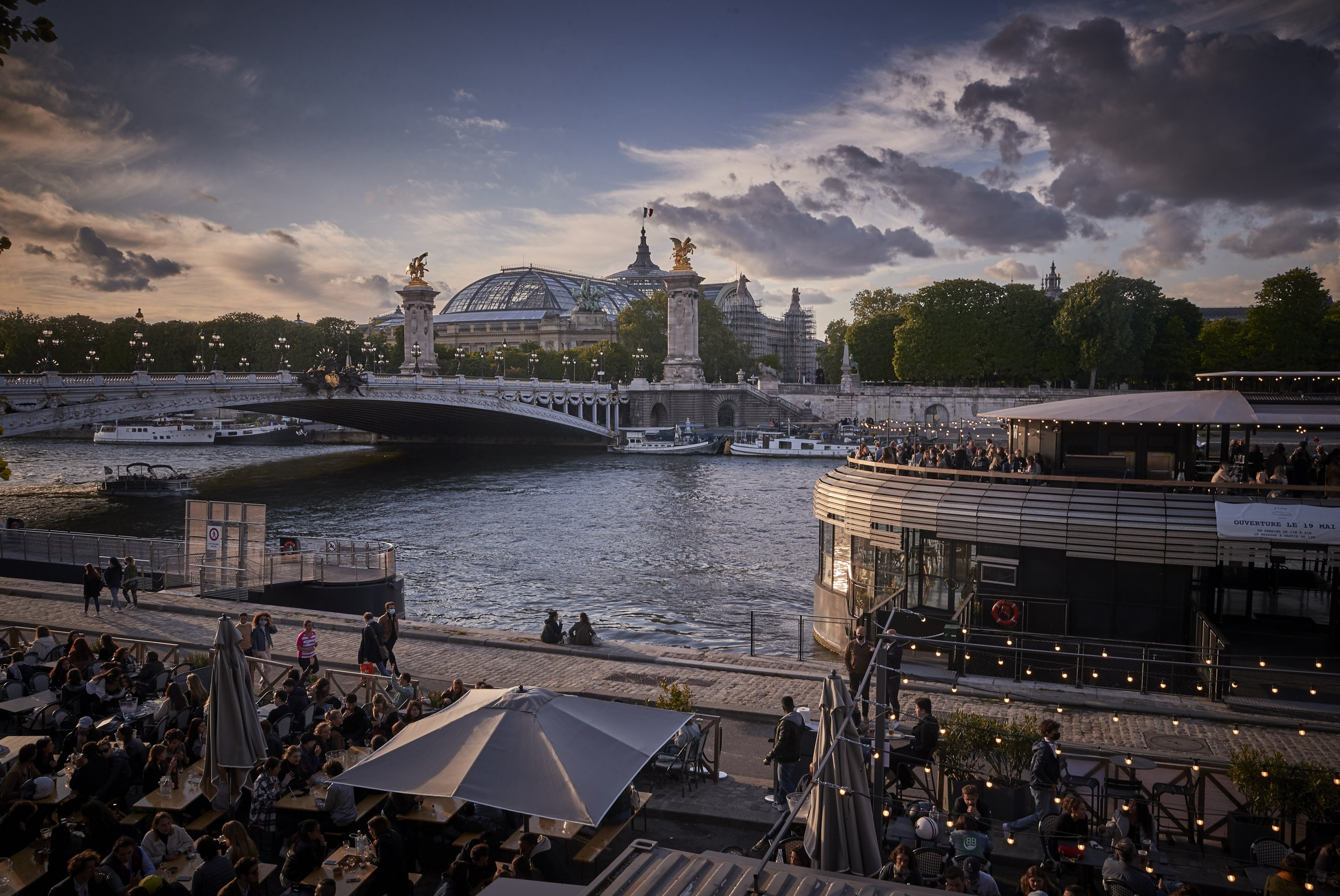 People enjoy the evening sun on the river Seine as cafes and restaurants across France reopen for the first time in over six months, after the coronavirus measures, Paris, France, May 19, 2021. (Photo by Getty Images)