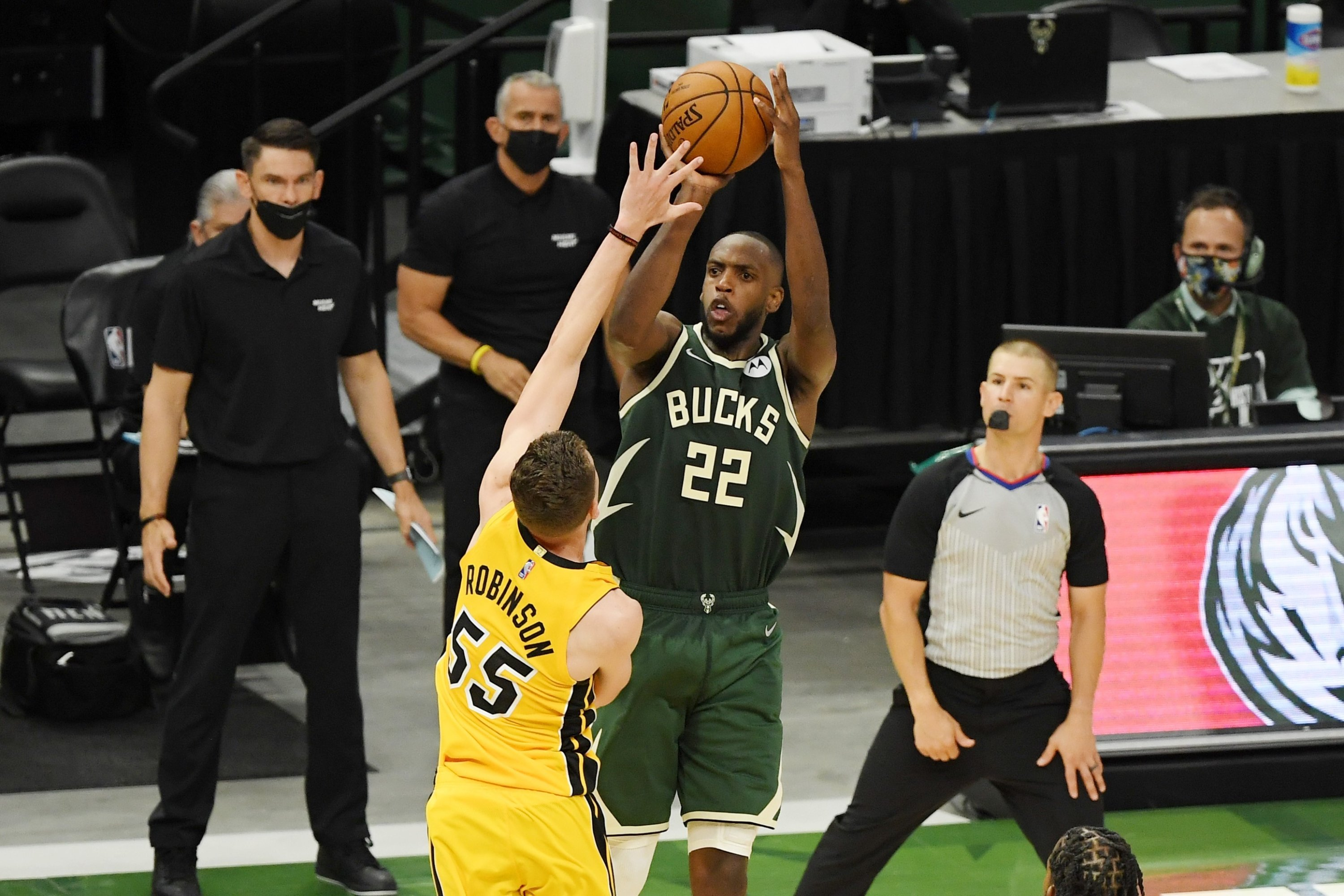 Milwaukee Bucks Khris Middleton (C) makes a basket in overtime against Miami Heat's Duncan Robinson during an NBA playoffs game at Fiserv Forum, Milwaukee, Wisconsin, U.S., May 22, 2021. (AFP Photo)