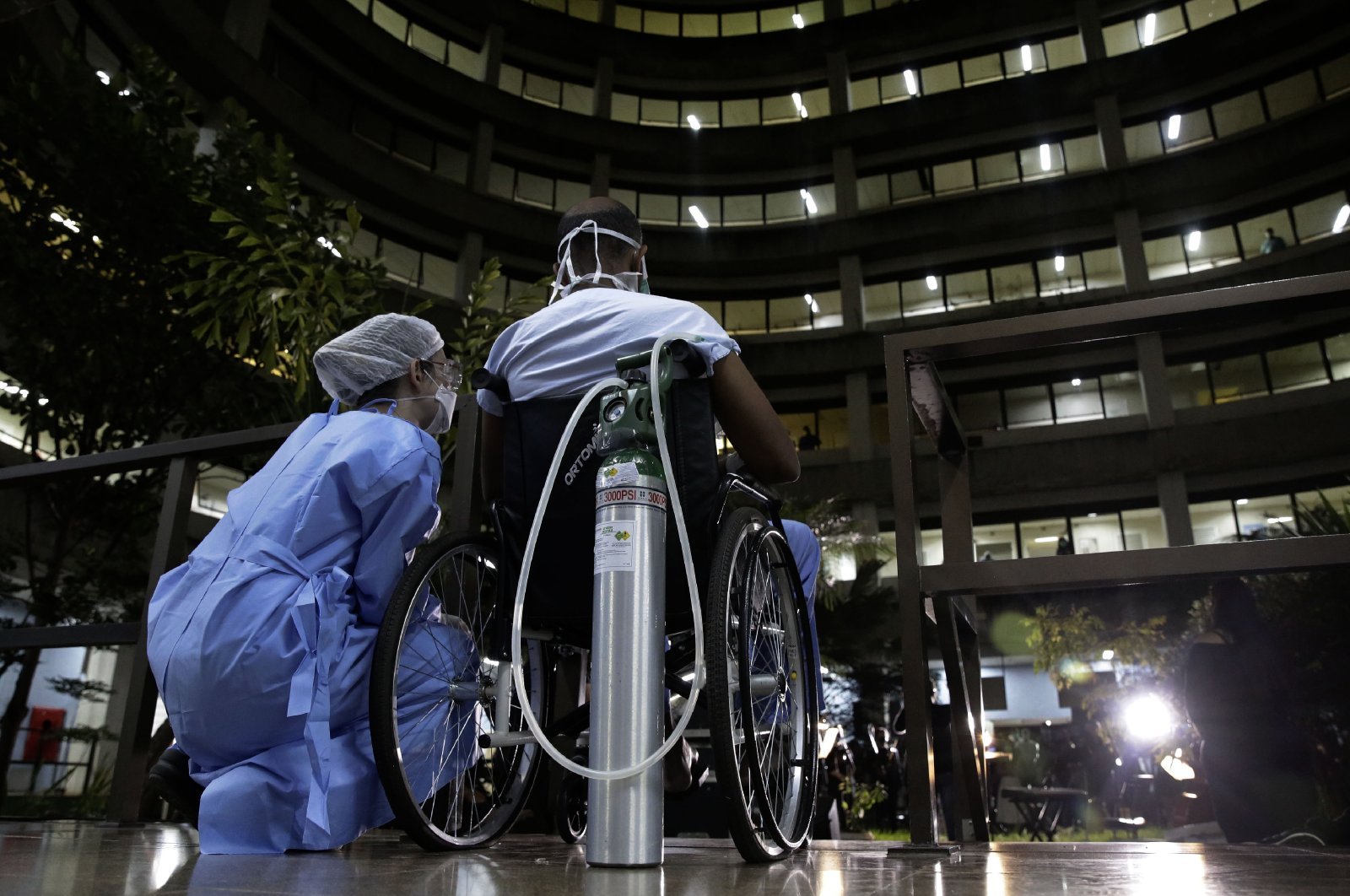 A nurse and her patient watch a performance by the Brasilia Philharmonic Orchestra, from the inner court of the HRAN Reference Hospital for COVID-19 in Brasilia, Brazil, Thursday, May 20, 2021. (AP Photo)