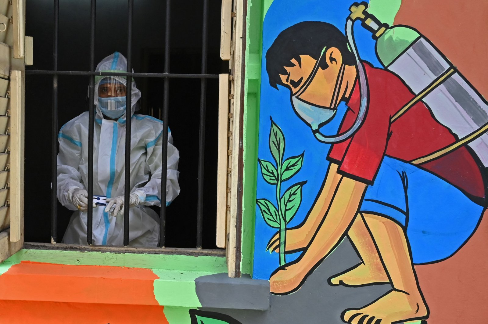 """A health worker wearing a protective suit stands in the window of a newly inaugurated """"Oxygen Hub"""" for COVID-19 patients in Kolkata, West Bengal, India, May 23, 2021. (AFP Photo)"""