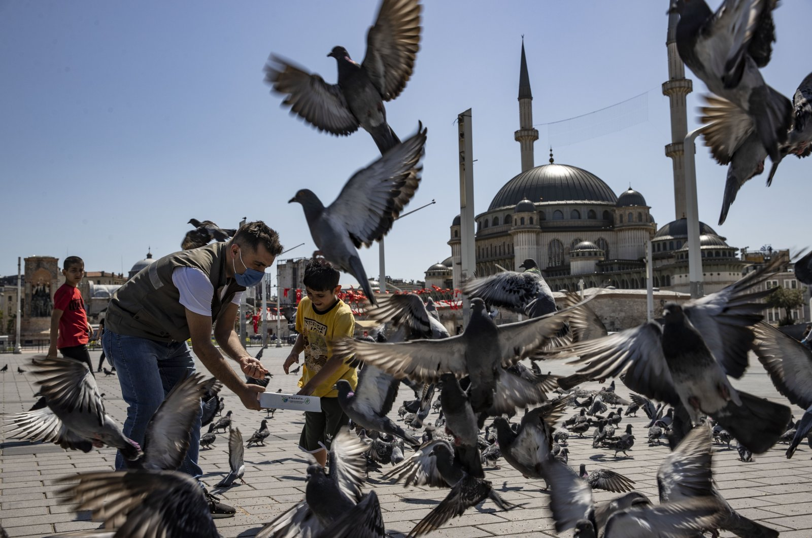 Turkish nature protection authorities help feed the birds and street animals during the total lockdown in Istanbul's famous Taksim Square, Turkey, May 15, 2021 (AA File Photo)