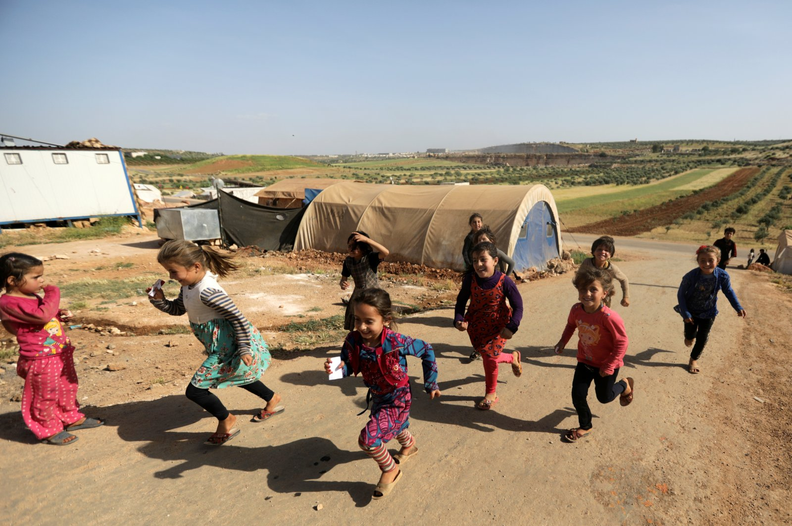 Internally displaced Syrian girls run together near tents at Teh camp in northern Idlib, Syria, May 5, 2021. (Reuters Photo)