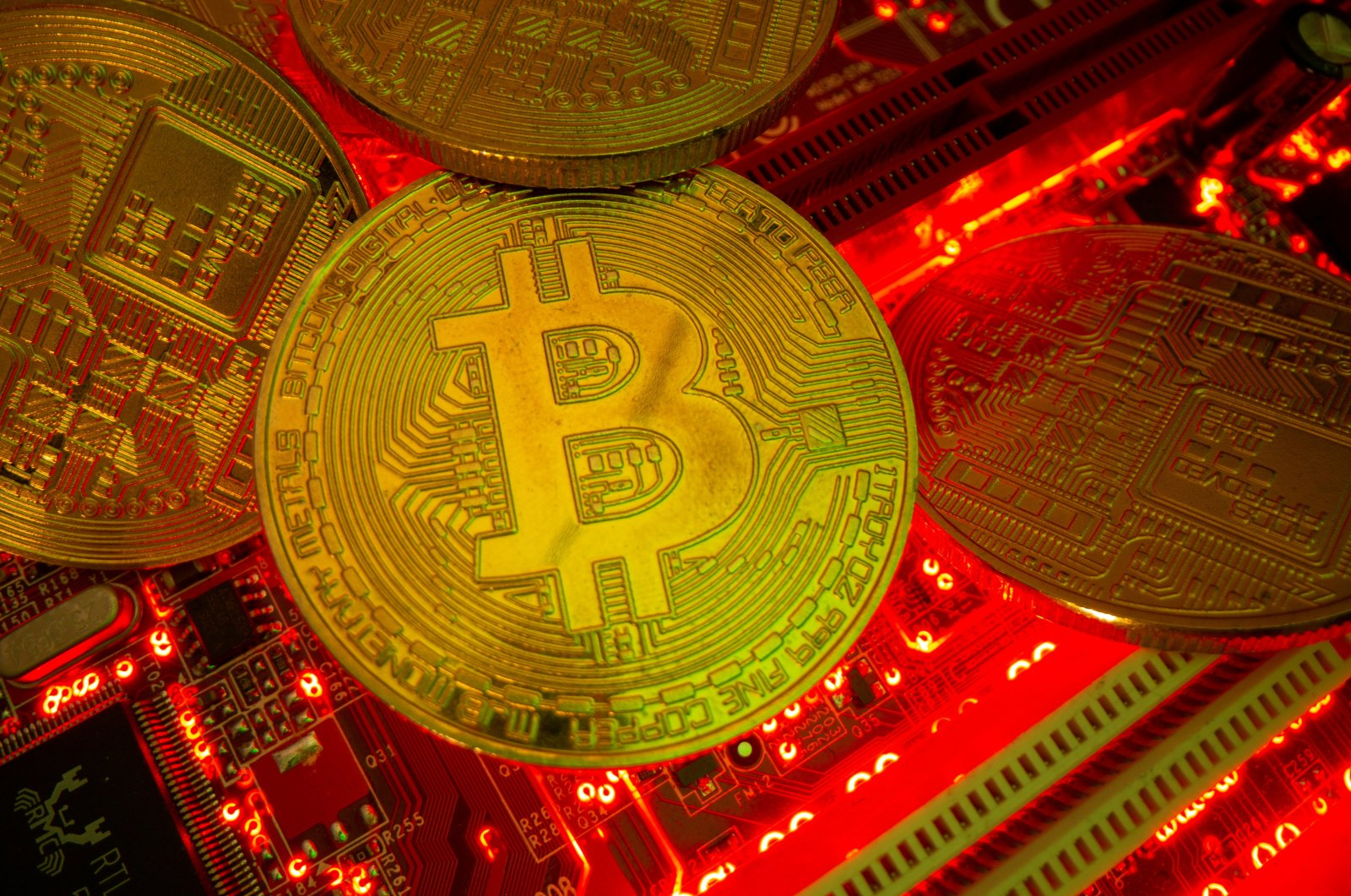 Representations of the virtual currency Bitcoin stand on a motherboard in this picture illustration taken May 20, 2021. (Reuters Photo)