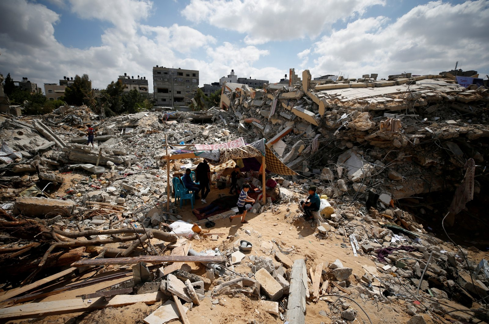 Palestinians sit in a makeshift tent amid the rubble of their houses that were destroyed by Israeli airstrikes during Israel's latest violence on the Gaza Strip, Palestine, May 23, 2021. (Reuters Photo)