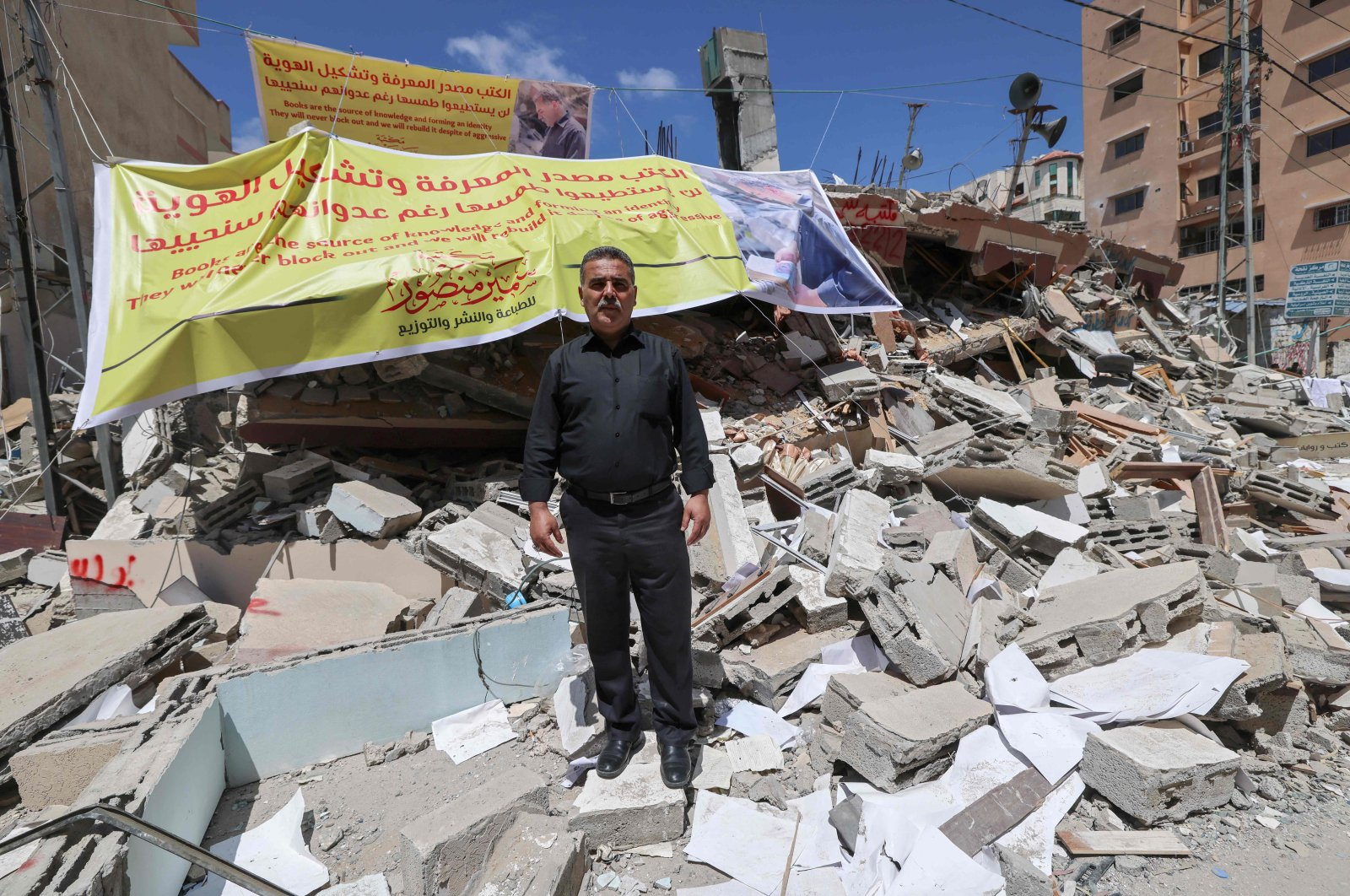 Samir Mansour, Palestinian owner of the eponymous bookstore and publishing house that had the largest collection of English literature in Gaza, standing in front of the rubble of his bookshop after it was destroyed by Israeli airstrikes, Gaza City, Palestine, May 22, 2021 (AFP Photo)