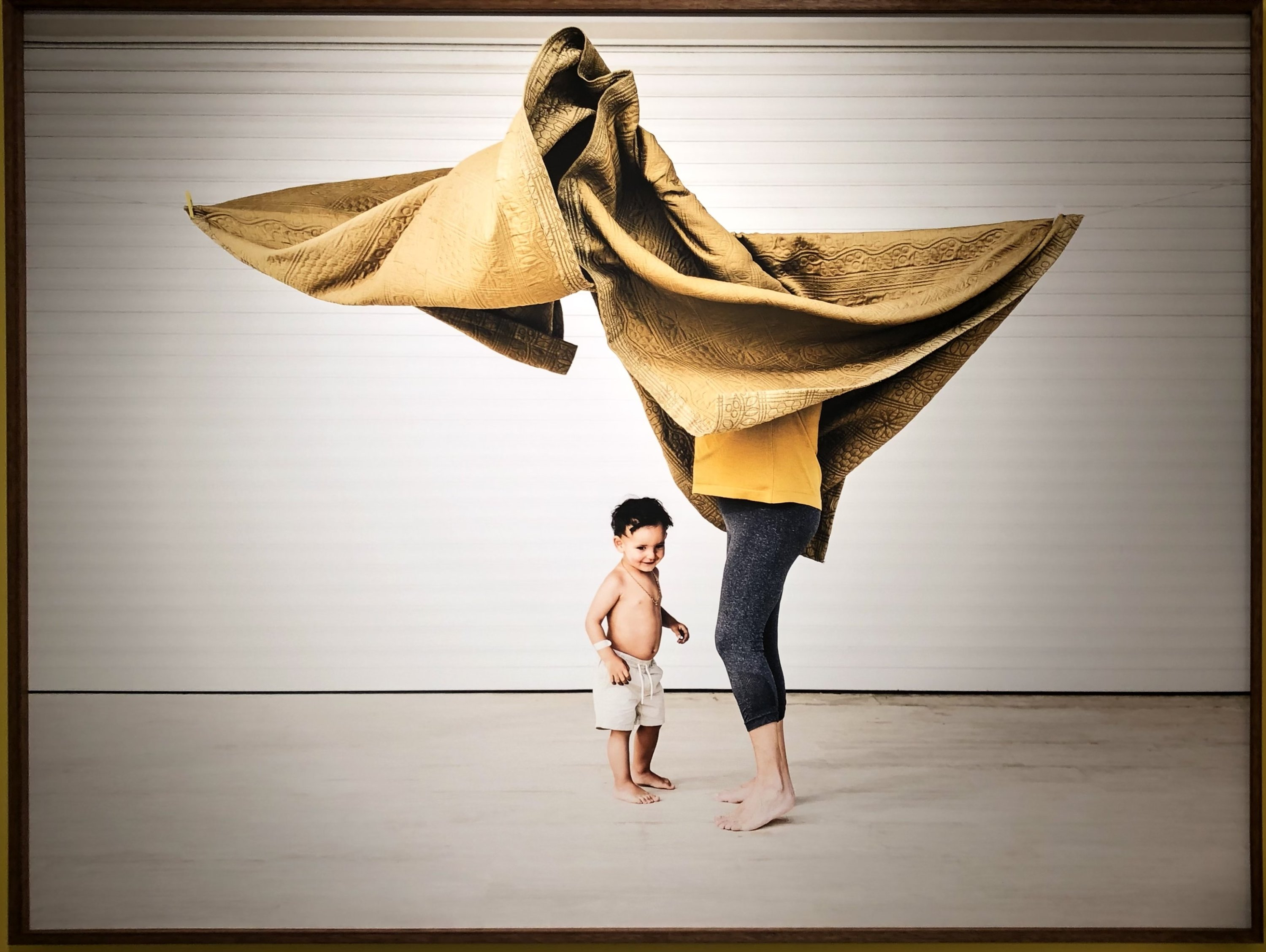 The photo depicts a motherly sort wearing a yellow shirt and playing with her child at the 'Double Portrait' by Cemre Yeşil. (Photo by Matt Hanson)