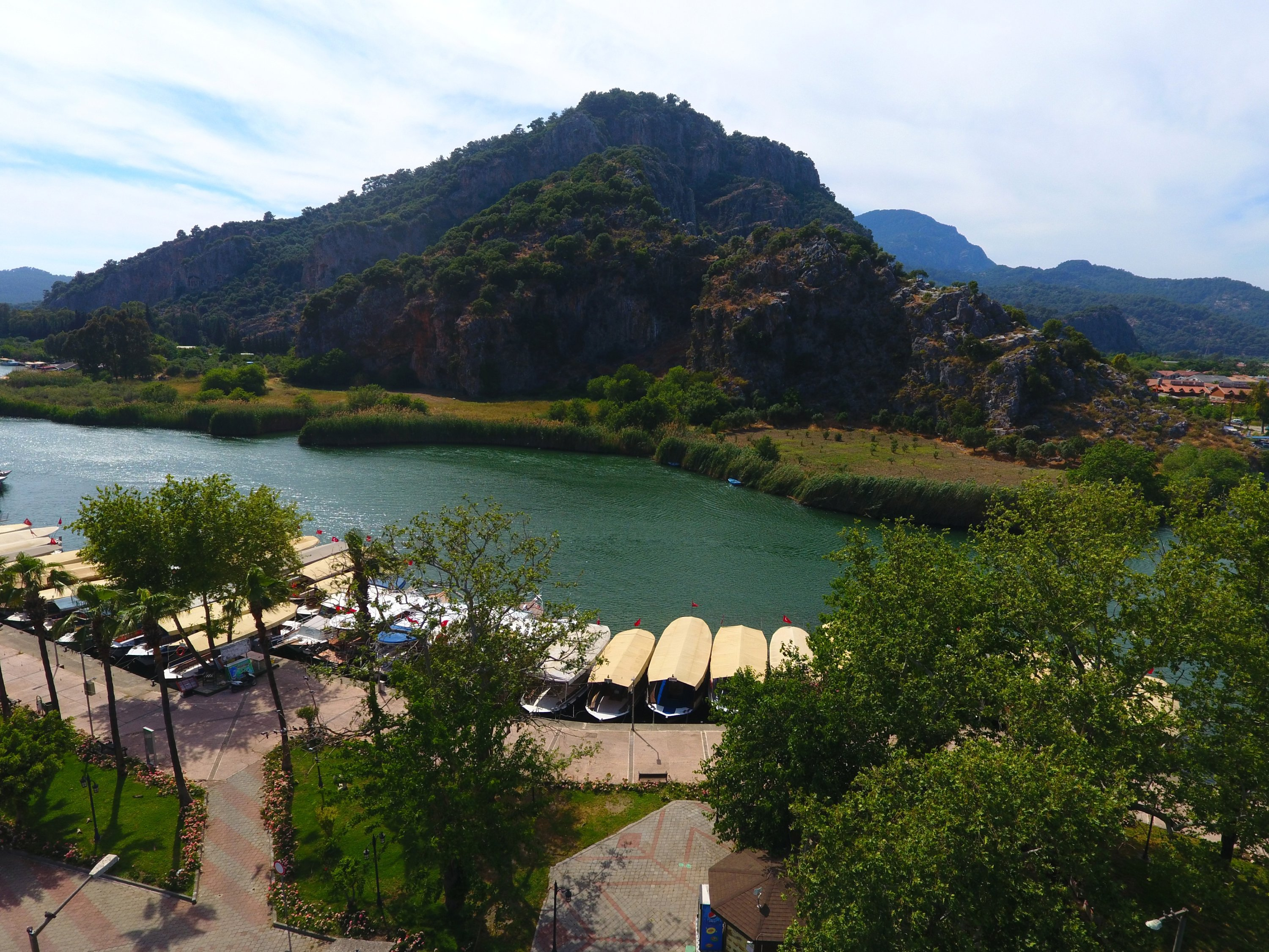 An aerial view showsboats floating on the waters of Dalyan river with forested mountainous areas in the background, Muğla, southwestern Turkey, May 19, 2021. (AA Photo)
