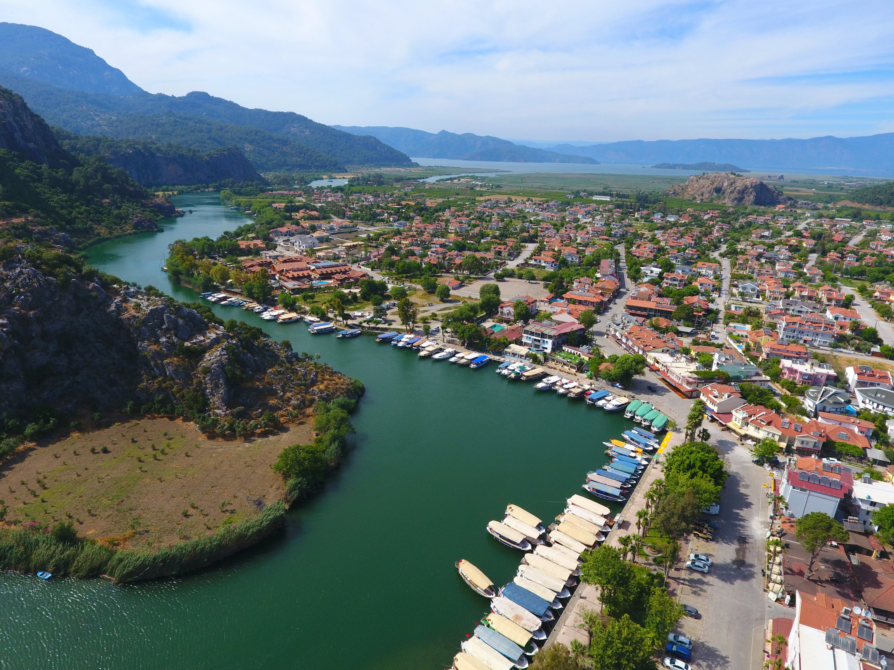 An aerial view showsboats floating on the waters of Dalyan river and the city of Dalyan, with forested mountainous areas in the background, Muğla, southwestern Turkey, May 19, 2021. (AA Photo)
