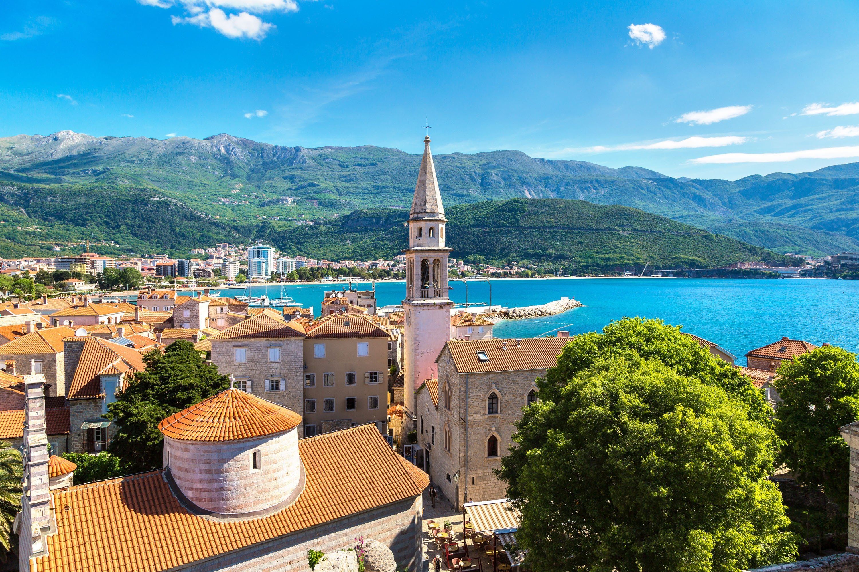 With the Adriatic Sea in the background, the bell tower of a church sticks out from the skyline of Budva's Altstadt, or Old Town, Montenegro. (Shutterstock Photo)