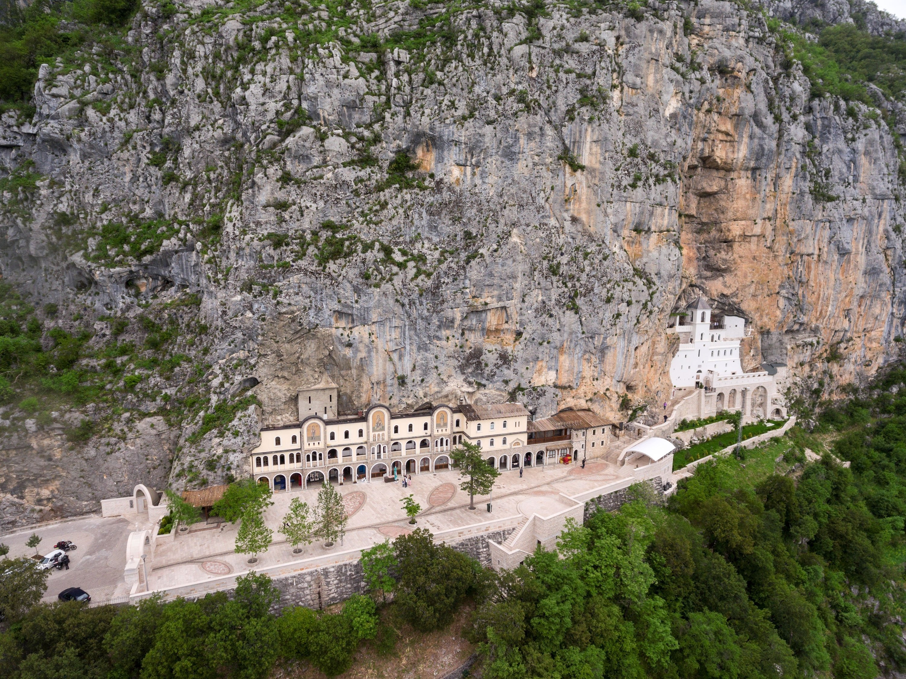 The Church of thePresentation and the Church of the Holy Cross stand situated against an almost vertical background of theOstroska Greda cliff, Montenegro. (Shutterstock Photo)