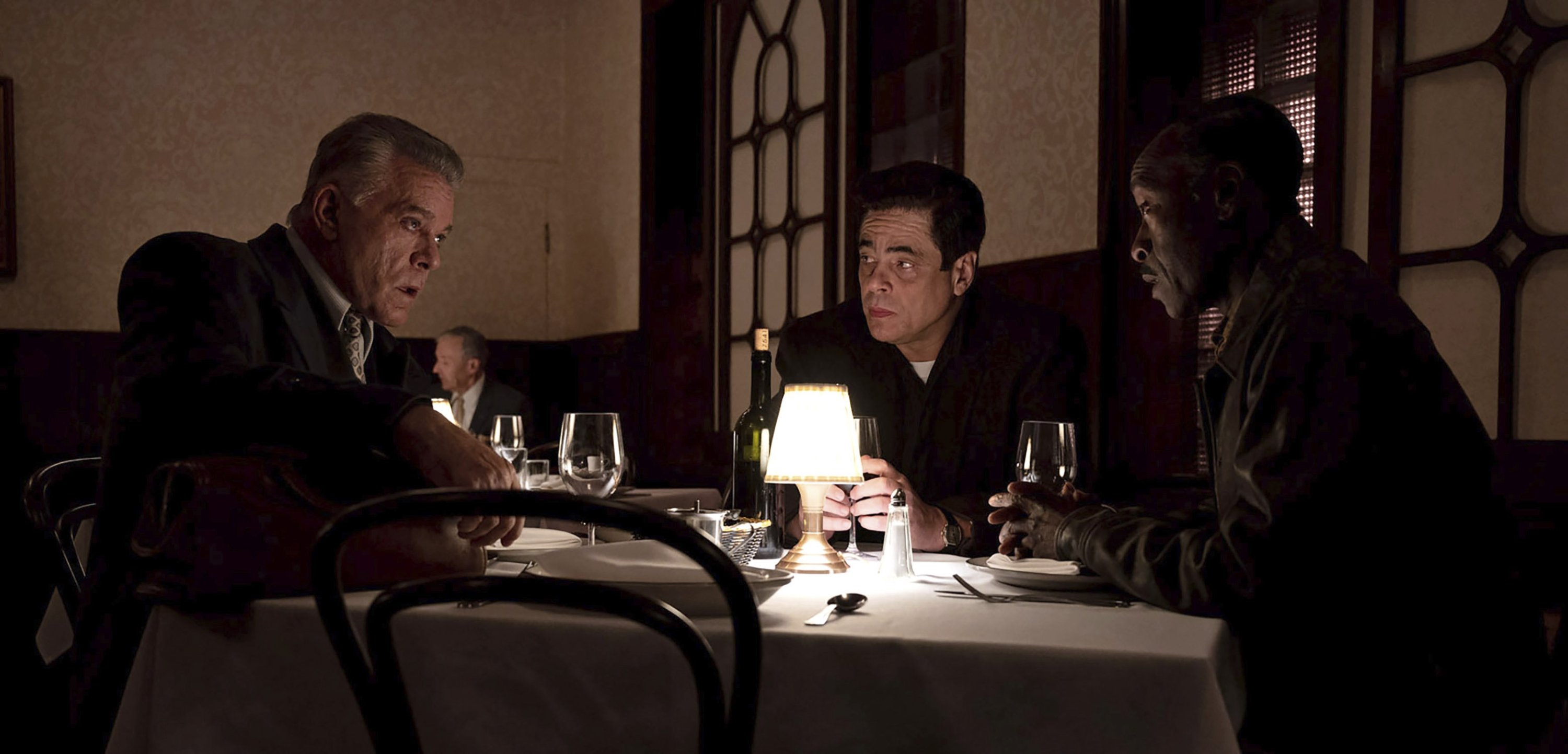 Ray Liotta (L), Benicio del Toro (C) andDon Cheadletalk while sitting at a restaurant table, in a scene from Steven Soderbergh's 'No Sudden Move,' a film that will premiere as the centerpiece of the Tribeca Film Festival next month. (Warner Bros. Pictures via AP)