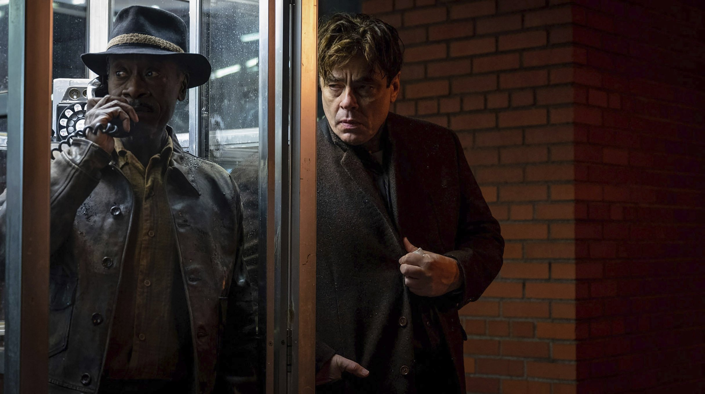 Don Cheadle (L) talks on the phone with Benicio del Toro alongside him, in a scene from Steven Soderbergh's 'No Sudden Move,' a film that will premiere as the centerpiece of the Tribeca Film Festival next month. (Warner Bros. Pictures via AP)