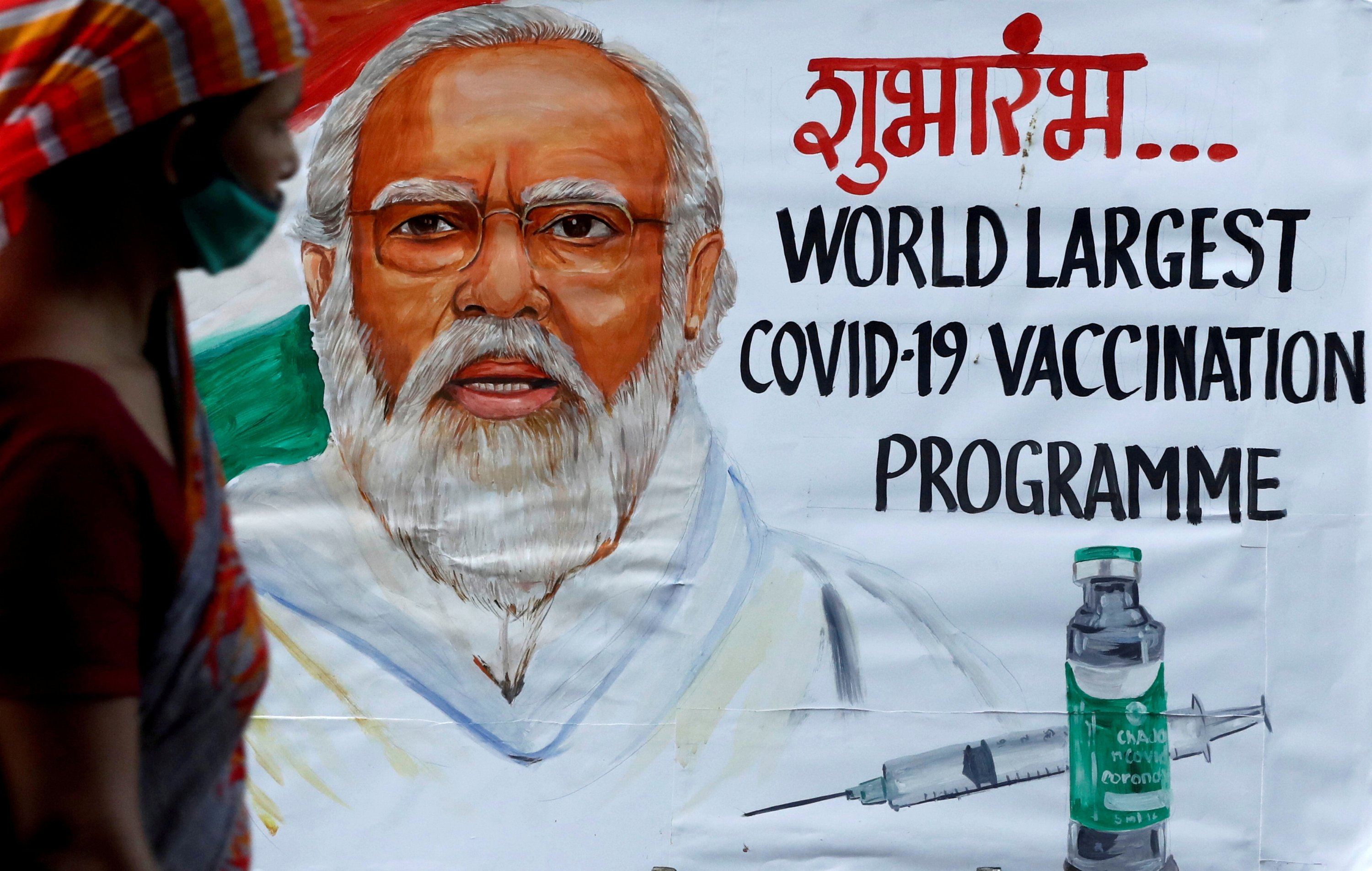 A woman walks past a painting of Indian Prime Minister Narendra Modi a day before the inauguration of the COVID-19 vaccination drive, on a street in Mumbai, India, Jan. 15, 2021. (REUTERS/File Photo)