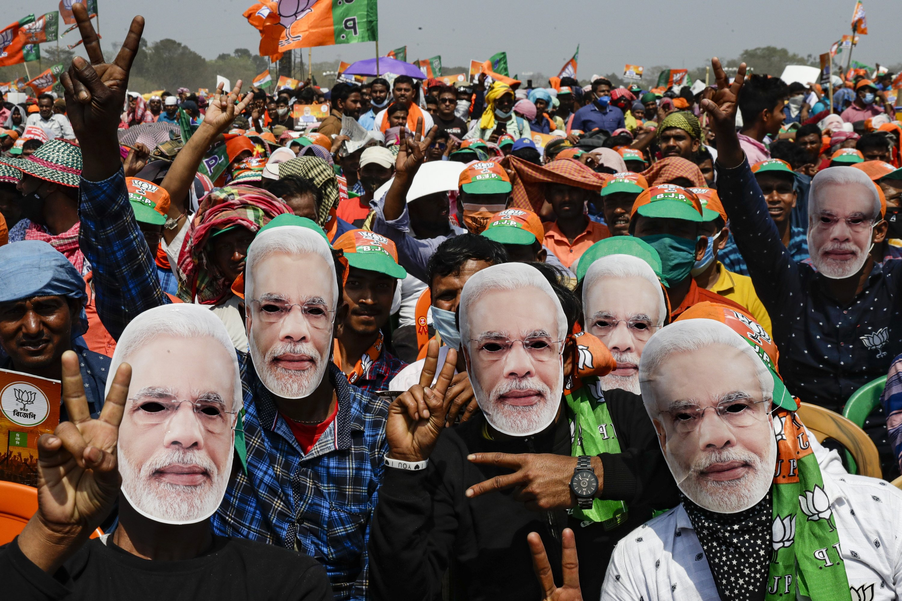 Bharatiya Janata Party (BJP) supporters wear masks of Prime Minister Narendra Modi as they gather for a rally addressed by Modi ahead of West Bengal state elections in Kolkata, India, March 7, 2021. (AP Photo/File)