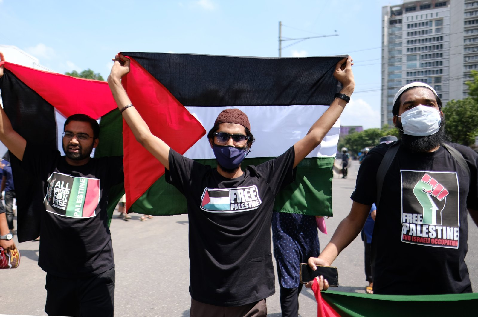 Bangladeshi men hold Palestinian flags as they participate in a protest against the Israeli attacks on Palestinians in Gaza, in Dhaka, Bangladesh, May 21, 2021. (AP Photo)