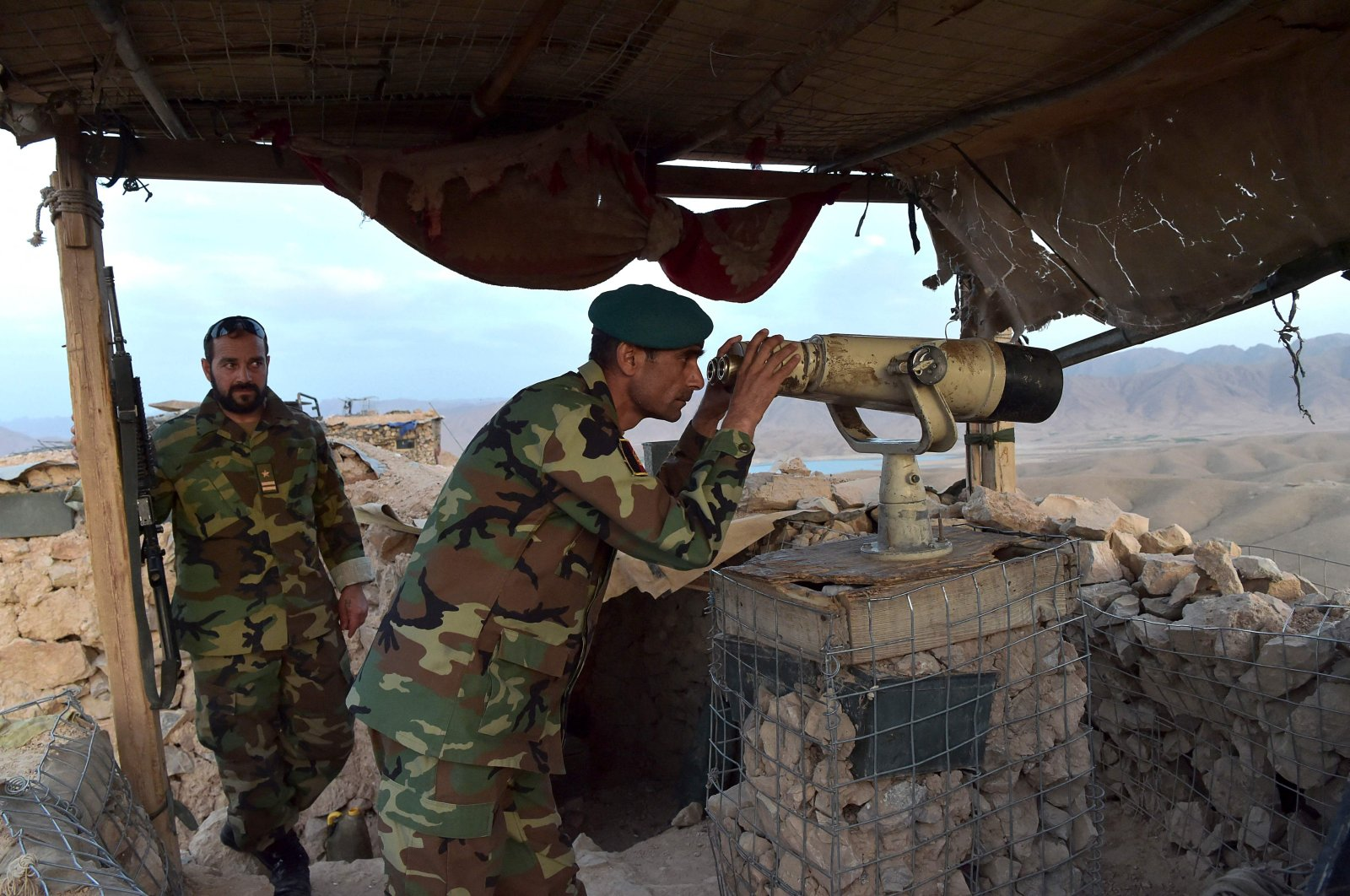 Afghan National Army (ANA) commander Dost Nazar Andarabi keeps watch with binoculars at an outpost set up against Taliban fighters in Kajaki, northeast of Helmand Province, Afghanistan, March 23, 2021. (AFP Photo)