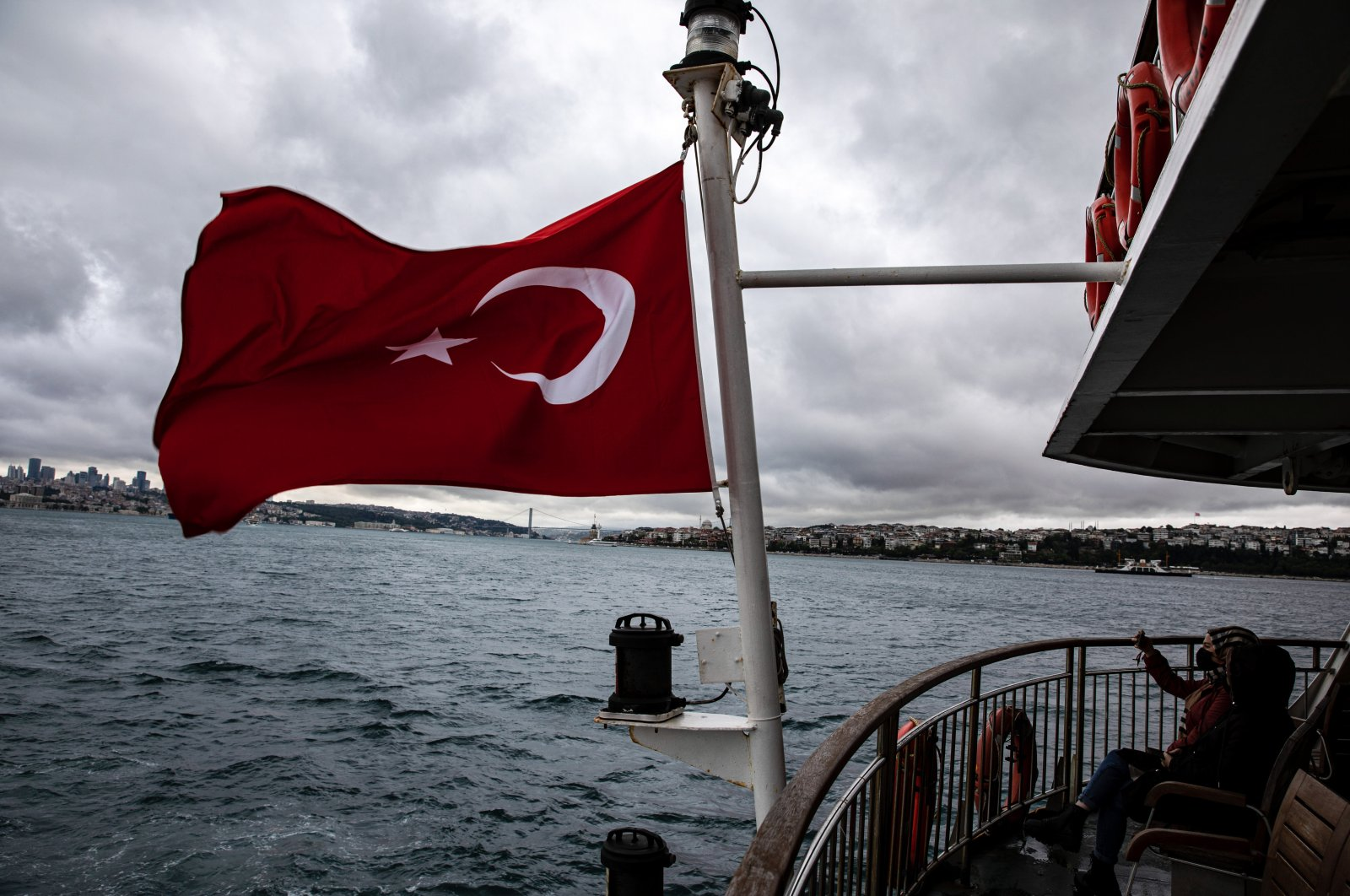 People traveling on a ferry from the Eminönü district to the Kadıköy district take pictures on a cloudy day, Istanbul, Turkey, May 21, 2021. (Photo by Getty Images)