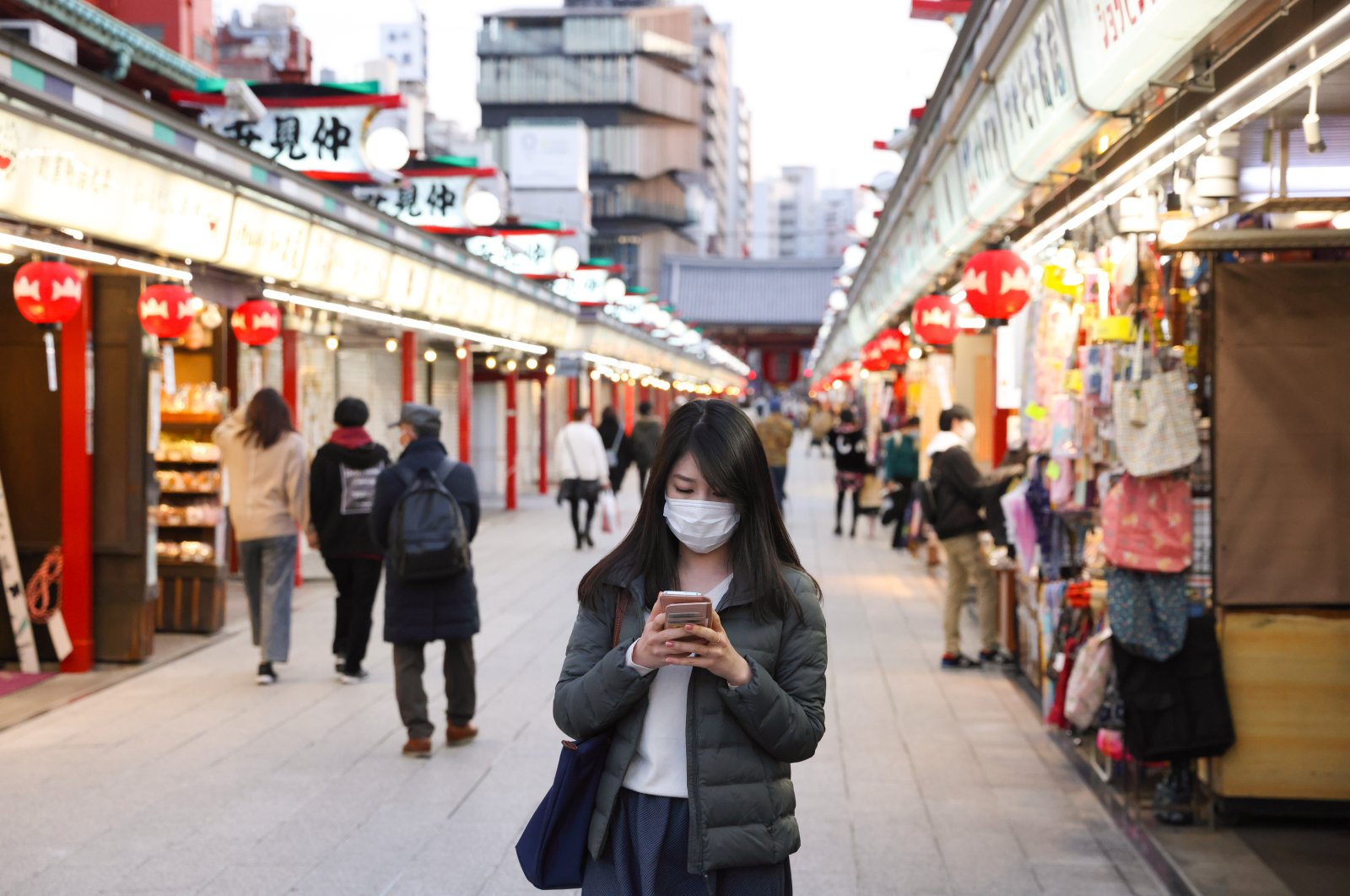 A woman wearing a mask walks through a shopping area of Asakusa Shrine, Tokyo, Japan, March 1, 2021. (Reuters Photo)