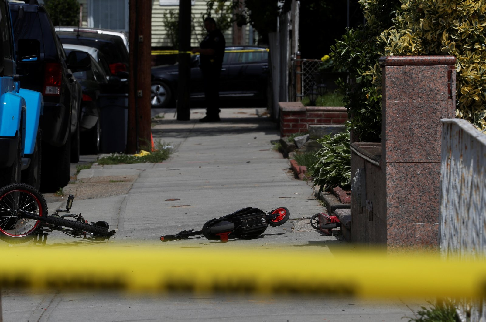 A New York police officer stands by police tape while small scooters and a bicycle lay on the sidewalk at a crime scene where three people were wounded, including an 8-year-old child, in a drive-by shooting in the Queens borough of New York City, the U.S., May 20, 2021. (Reuters Photo)