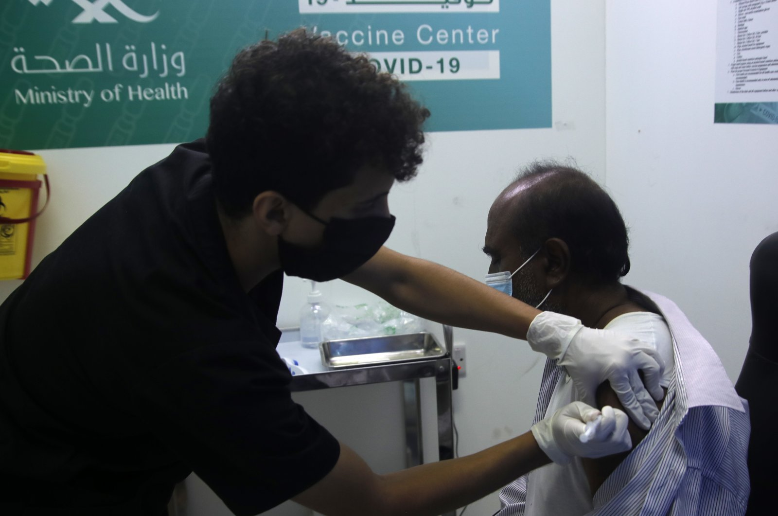 A Saudi physician administers a Pfizer coronavirus vaccine to a man at a vaccination center in the old Jeddah airport, Saudi Arabia, May 18, 2021. (AP Photo)