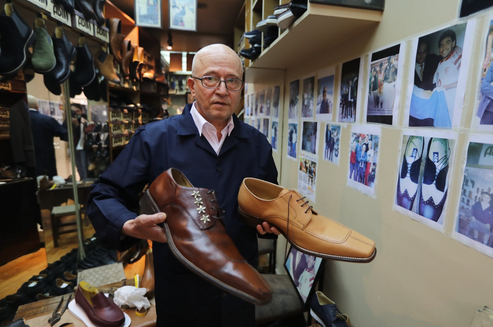 Shomaker Öncel Kalkan poses with the large-size shoes he made in his shop in Beyoğlu, Istanbul, Turkey, May 24, 2021. (AA Photo)