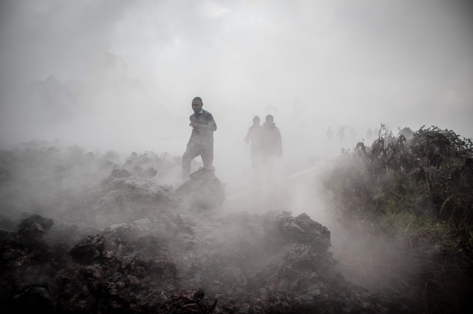 Men cross the front of the still-smoking lava rocks from an eruption of Mount Nyiragongo, Goma, the Democratic Republic of Congo, May 23, 2021. (AFP Photo)
