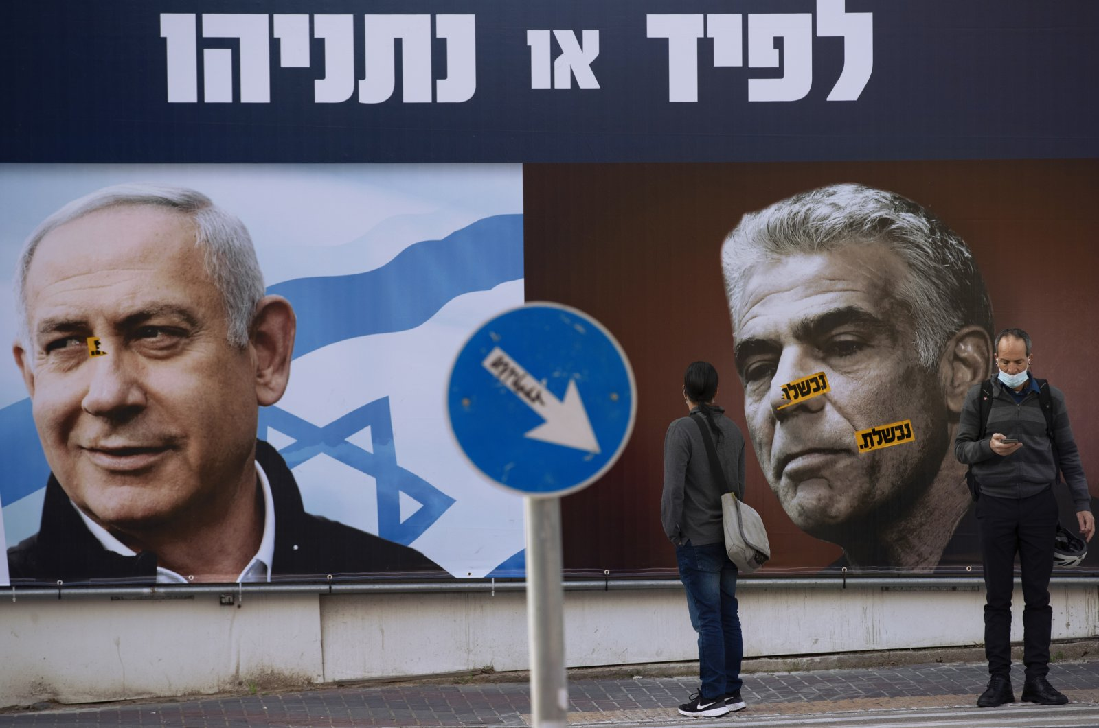 People stand in front of an election campaign billboard for the Likud party showing a portrait of its leader Prime Minister Benjamin Netanyahu (L) and opposition party leader Yair Lapid, in Ramat Gan, Israel, March 14, 2021. (AP Photo)