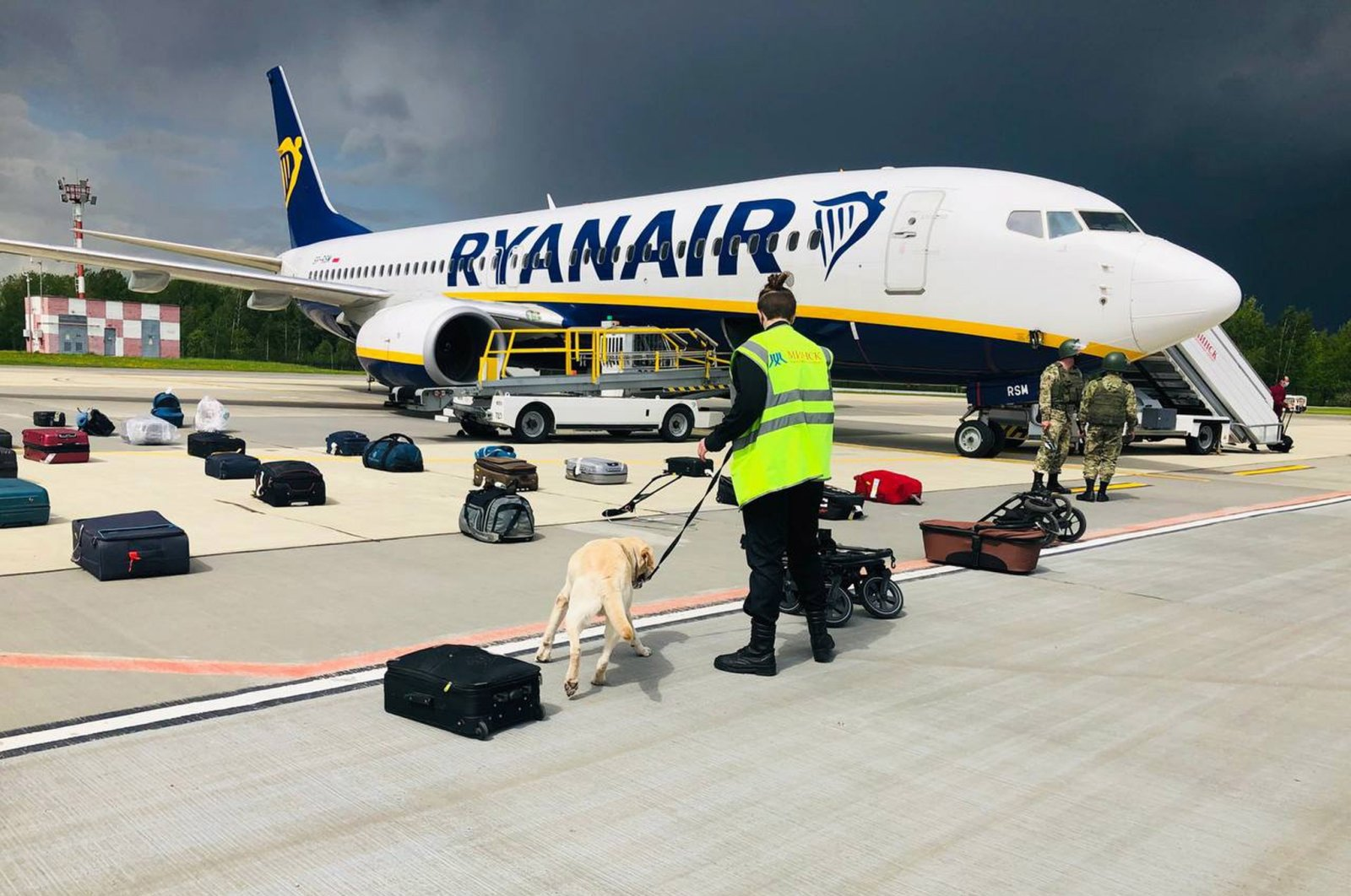 Security with a sniffer dog checks the luggage of passengers in front of the Ryanair Boeing 737-8AS (flight FR4978), carrying opposition figure Roman Protasevich, in Minsk, Belarus, May 23, 2021. (EPA Photo / ONLINER.BY handout photo)