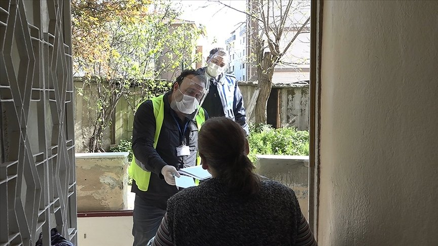Social aid workers hand out cash aid to a woman in her home during the lockdown, in the capital, Ankara, Turkey, May 6, 2021.